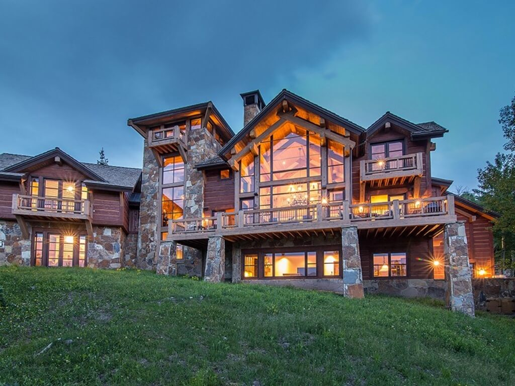 Rear view of the home showcasing abundance of large windows, exposed beam and vaulted ceiling construction, stone foundation and support, and array of wood balconies.