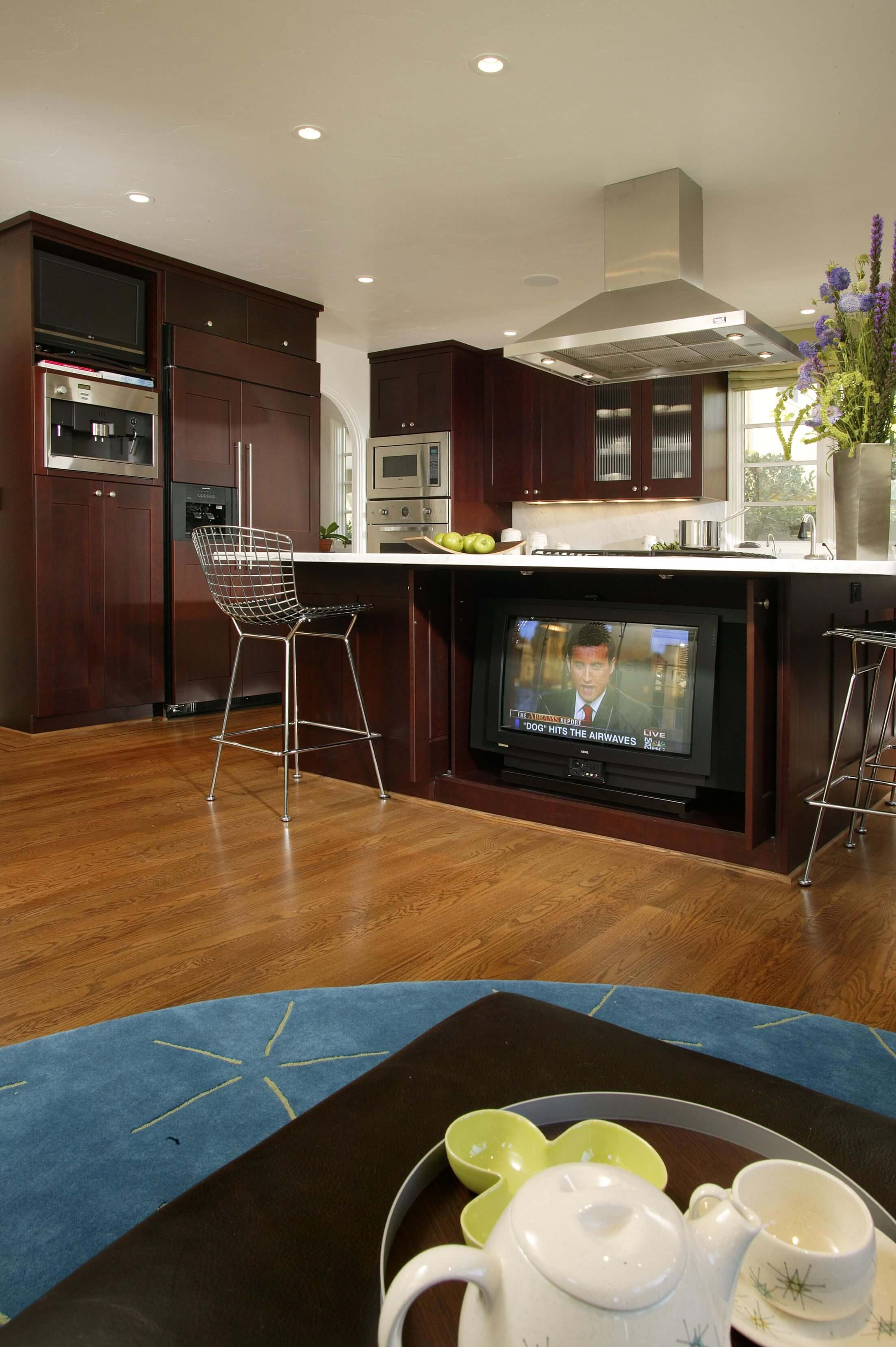 Large, open plan kitchen featuring natural hardwood flooring, with dark wood cabinetry throughout, punctuated by brushed aluminum appliances.