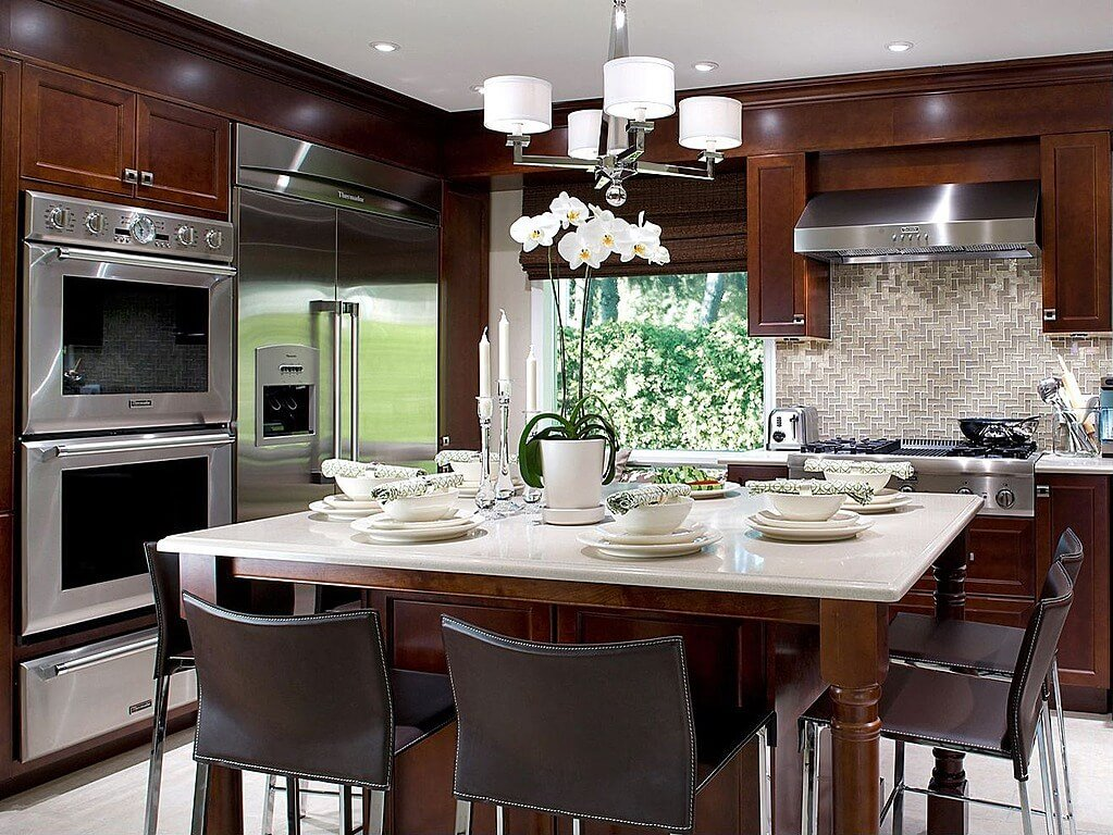 Bright marble countertops and matching tile flooring contrast with dark natural wood tones throughout this kitchen, enveloping brushed aluminum appliances and patterned tile backsplash.