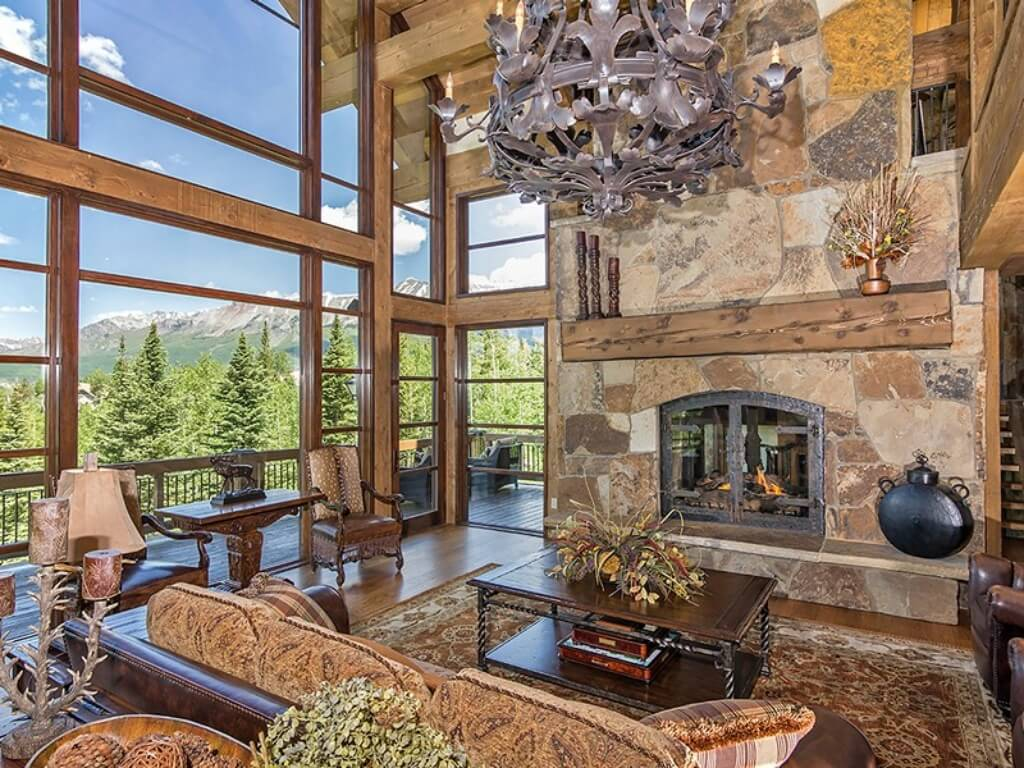 This is a close look at the living room that has a large mosaic stone fireplace on one side and a large glass wall on the other that brings in natural lights for the brown leather sofa set and wooden coffee table on the patterned area rug.
