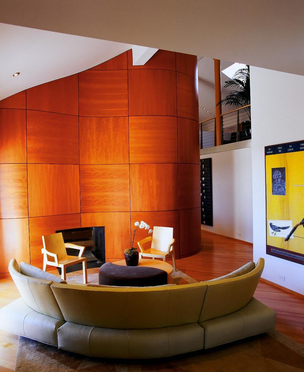 Modern semi-circular sectional couch wraps around yin-yang table in this living room flush with cherry wood, on flooring and large wave-shaped panel wall.