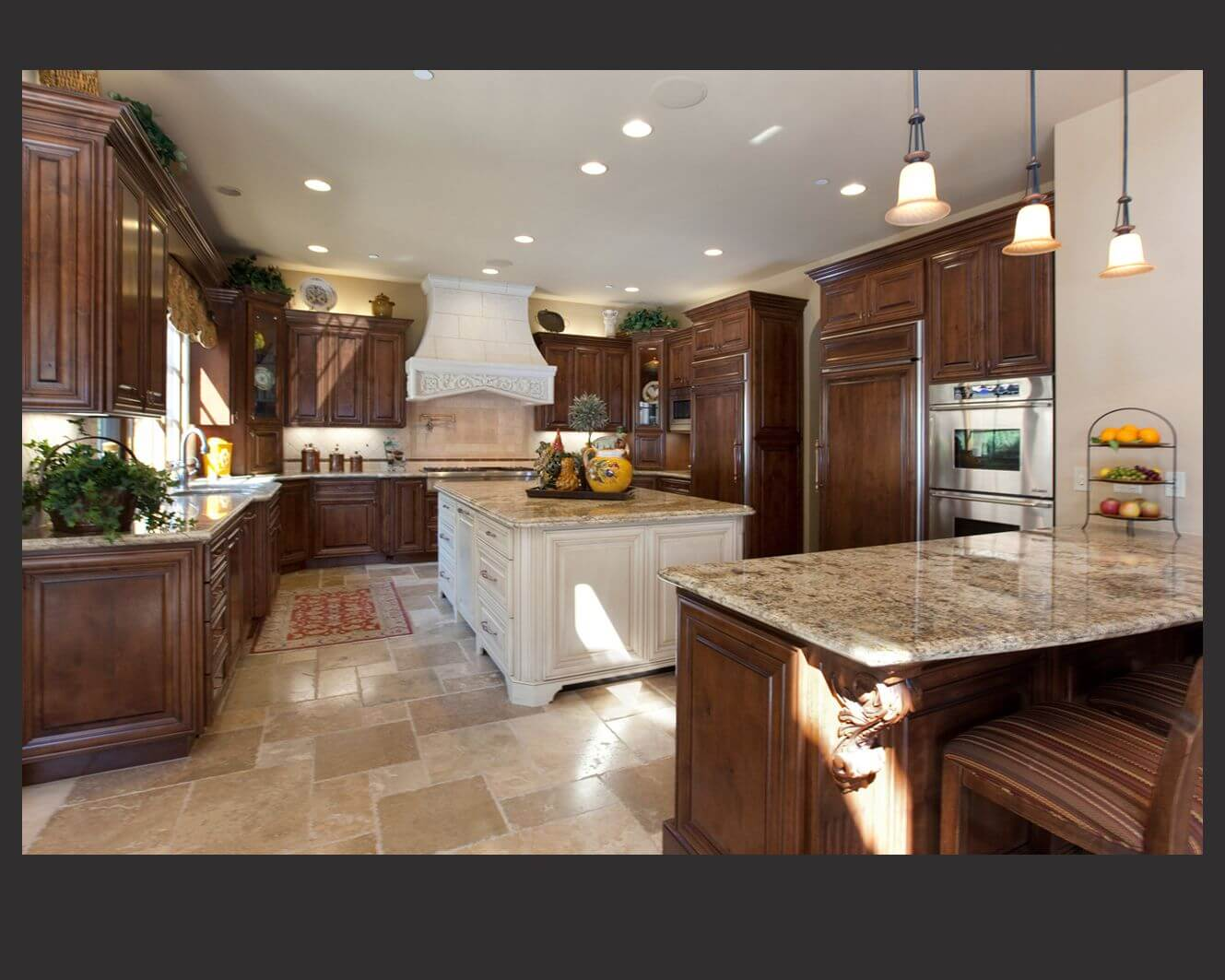 Richly detailed U-shaped kitchen centers dark wood cabinetry around large, white painted wood island with beige marble counters all around.