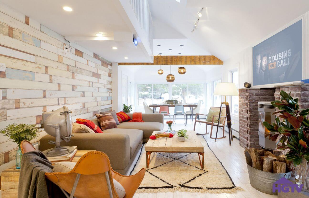 This bright living room featuring textured wood panel wall under white balcony, with brick fireplace surround across light wood flooring, holds light brown sectional with chaise lounge and large coffee table with natural wood over metal supports. Dining area with exposed beam above sits in background.