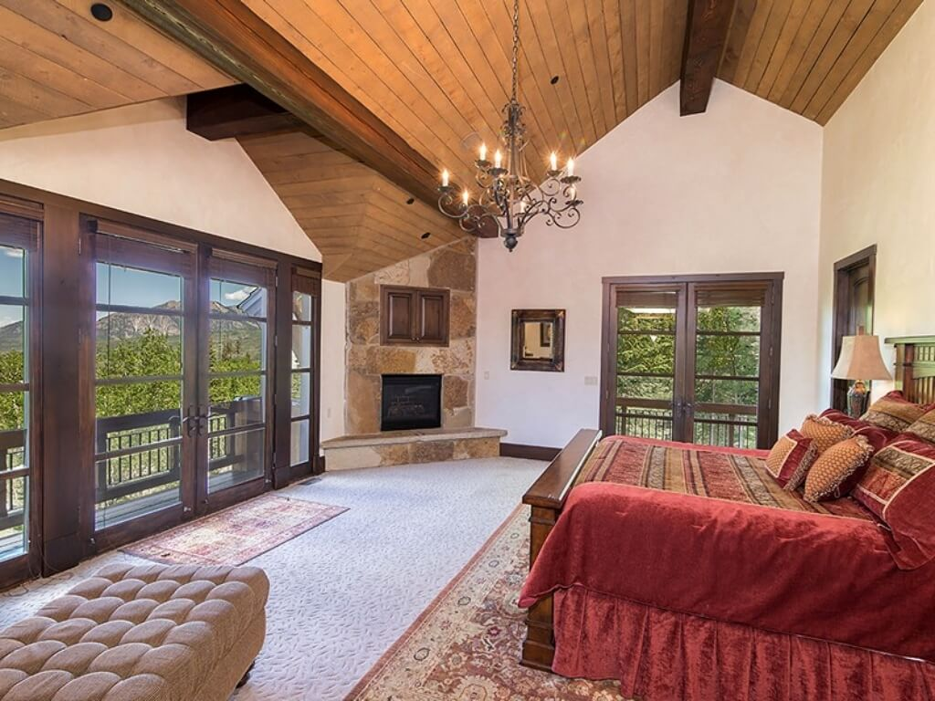 This bedroom features dark wood framed glass doors to balcony, white carpeting, natural wood framed bed, and ornate chandelier hanging from vaulted ceiling with large exposed beams.