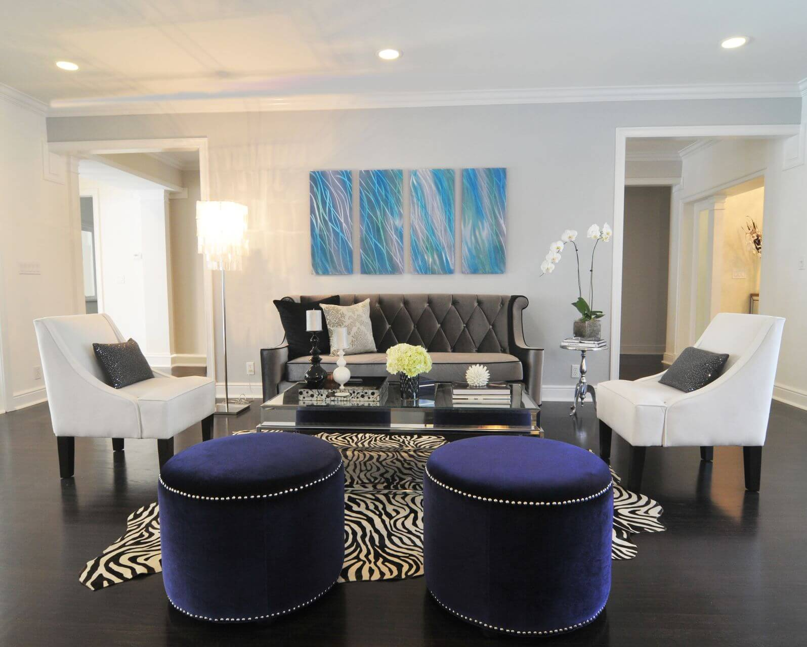 Small contemporary living room with dark floor on which is an abstract-shaped zebra print rug which is in the center of the room that contains a grey sofa, two white chairs and a glass coffee table