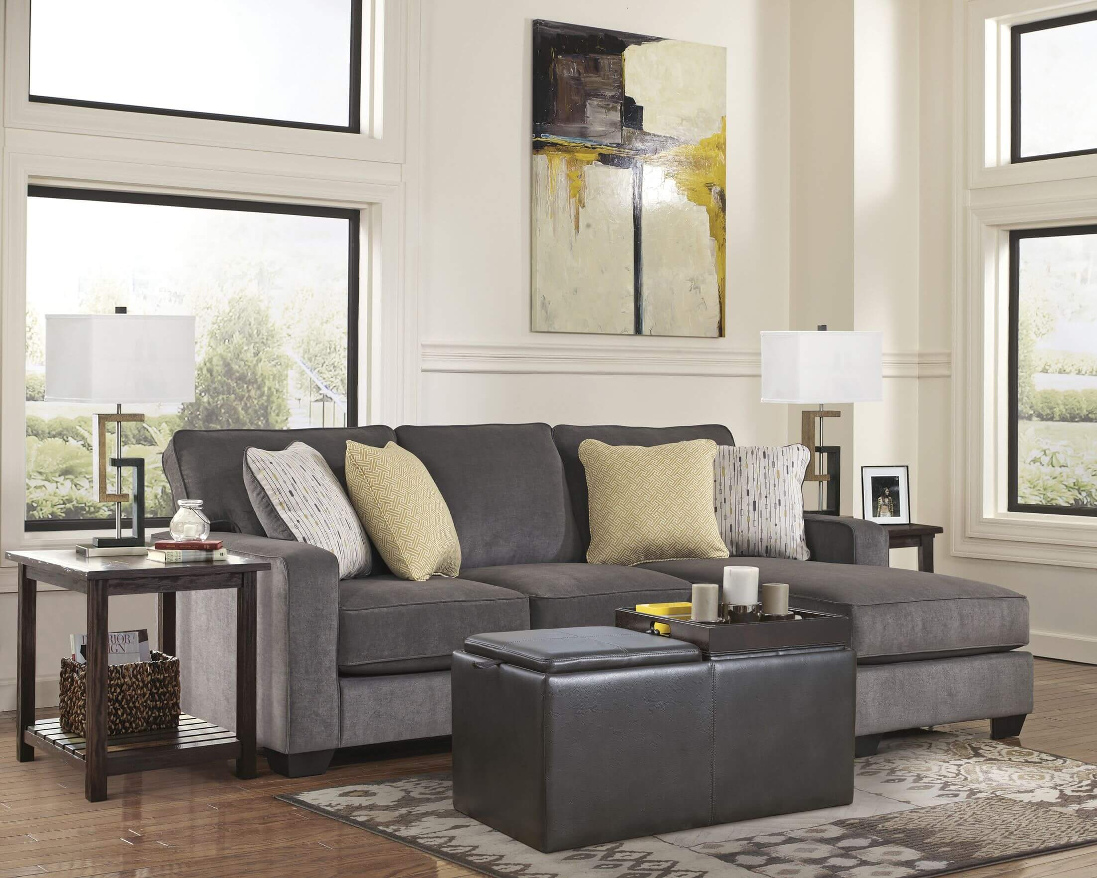 This cozy space features a simple and direct cushion backed sectional couch with built-in chaise lounge, with matching grey leather ottoman over natural hardwood flooring.