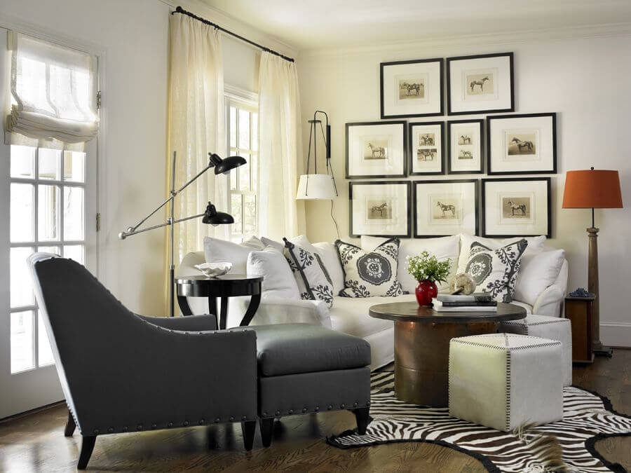 Cozy small living room in the situated in the corner of a larger space that contains a small zebra print rug, grey chair with matching ottoman, round wood coffee table and small white sofa