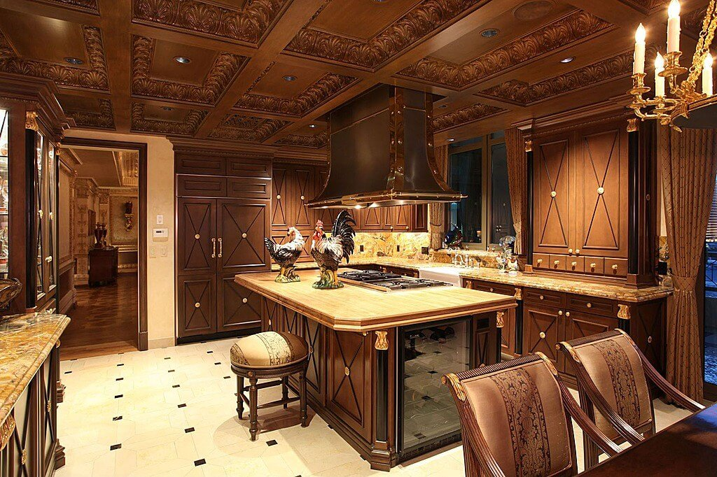 Lush carved wood cabinetry details abound in this kitchen featuring large natural wood topped island beneath filigreed raised ceiling detail.