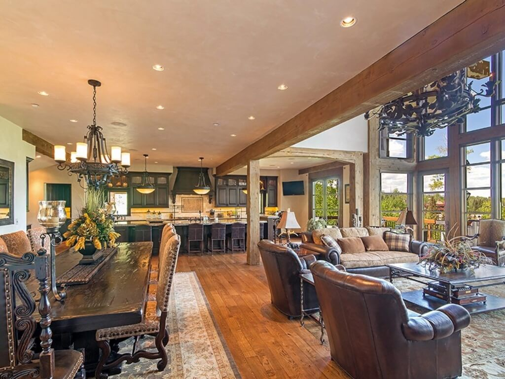 Open design central living room framed in massive exposed natural wood beams, featuring ornate dining space on left, spread of leather furniture in living room on right, and kitchen space in background.