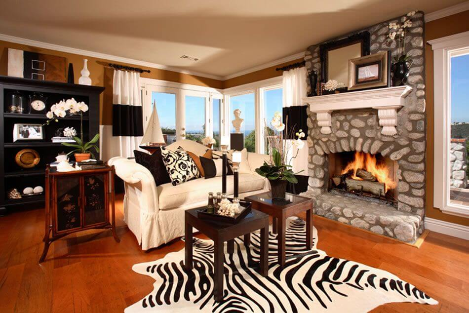 Cozy contemporary living room with wood floor, stone fireplace, white loveseat, two small square coffee tables situated on zebra print rug