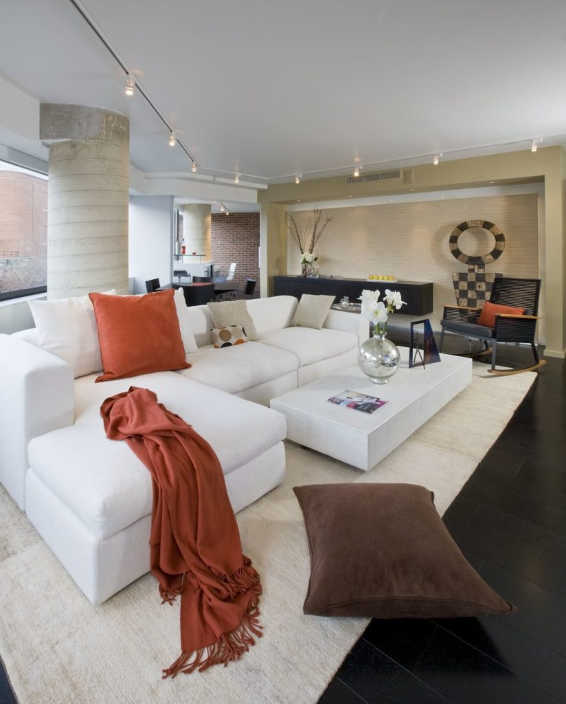 "Living room centers furniture on light area rug around ""floating"" coffee table in matching white. Embedded lighting in far wall highlights art pieces and similarly ""floating"" black wall-mounted cabinetry."