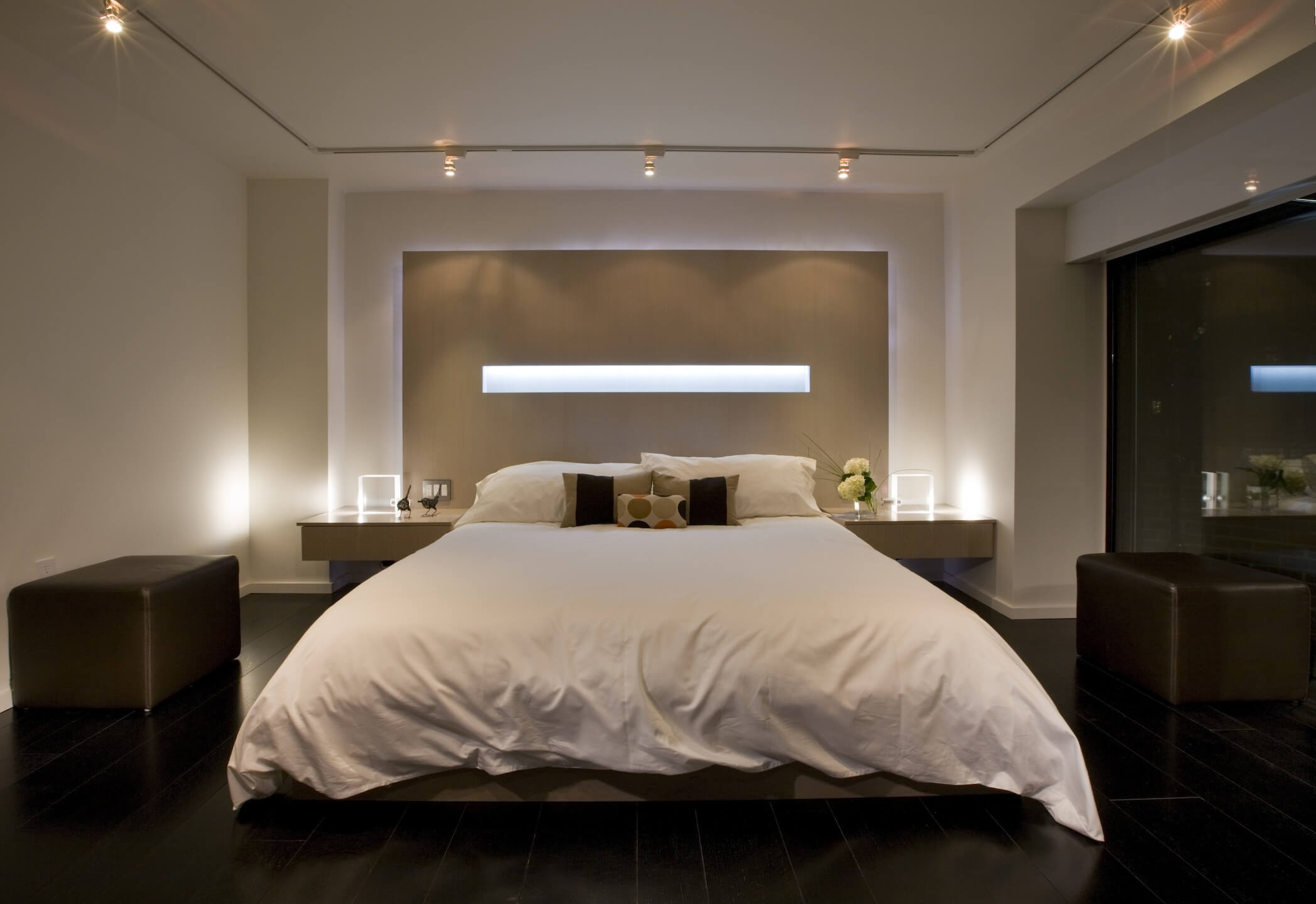 Head-on view of primary bedroom, showcasing white-covered bed in front of monolithic wall detail containing horizontal light strip. Large dark leather ottomans stand on each side.