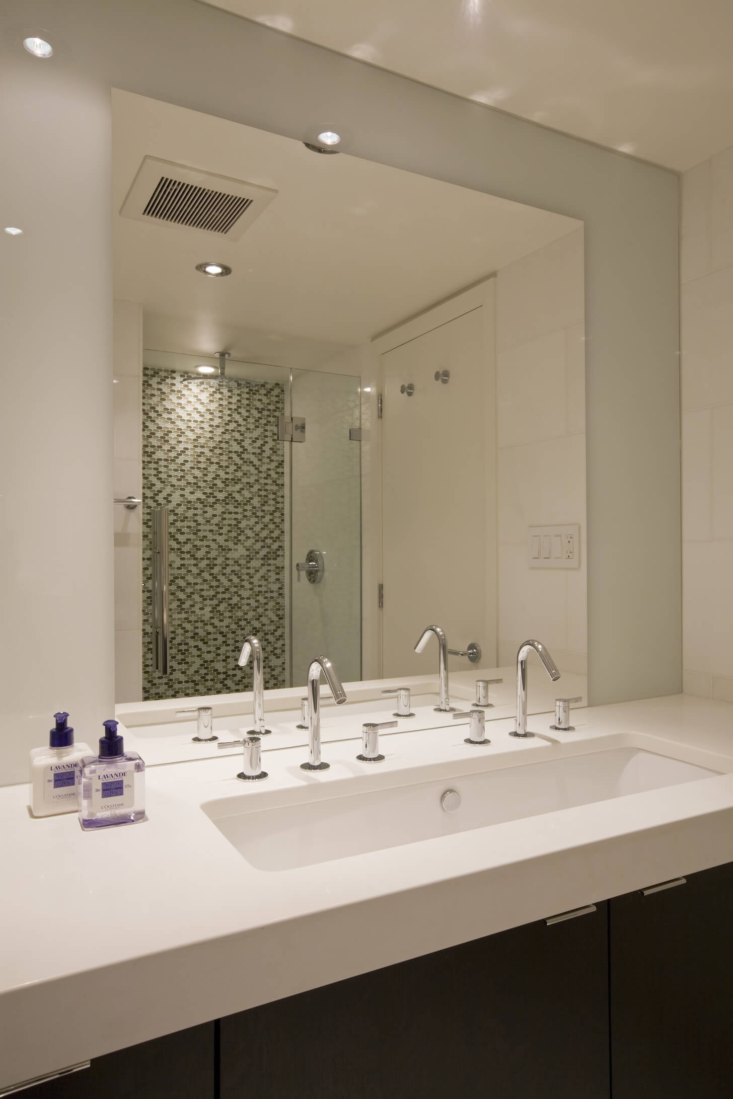 Close view of sink area reveals double-wide basin, while patterned tile, glass door shower is seen in reflection.