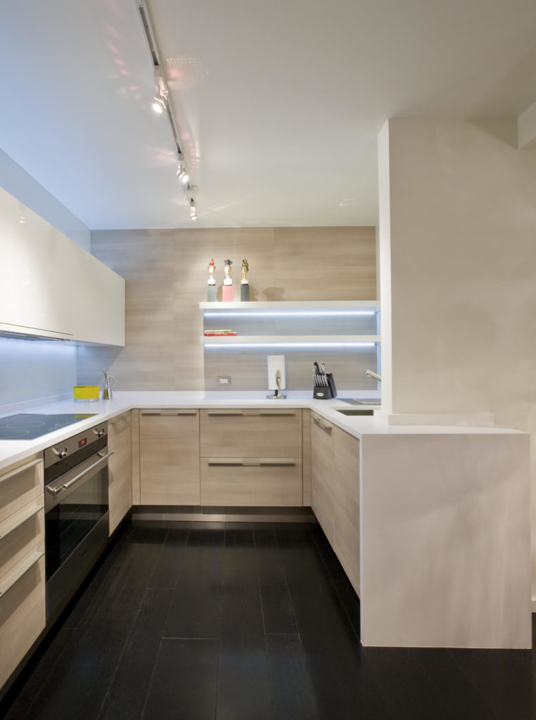 Kitchen viewed closely reveals glossy white countertop surface mirrored in wall-mounted shelving and cupboards above range. Again, subtle hidden light sources create a warm glow in this space.