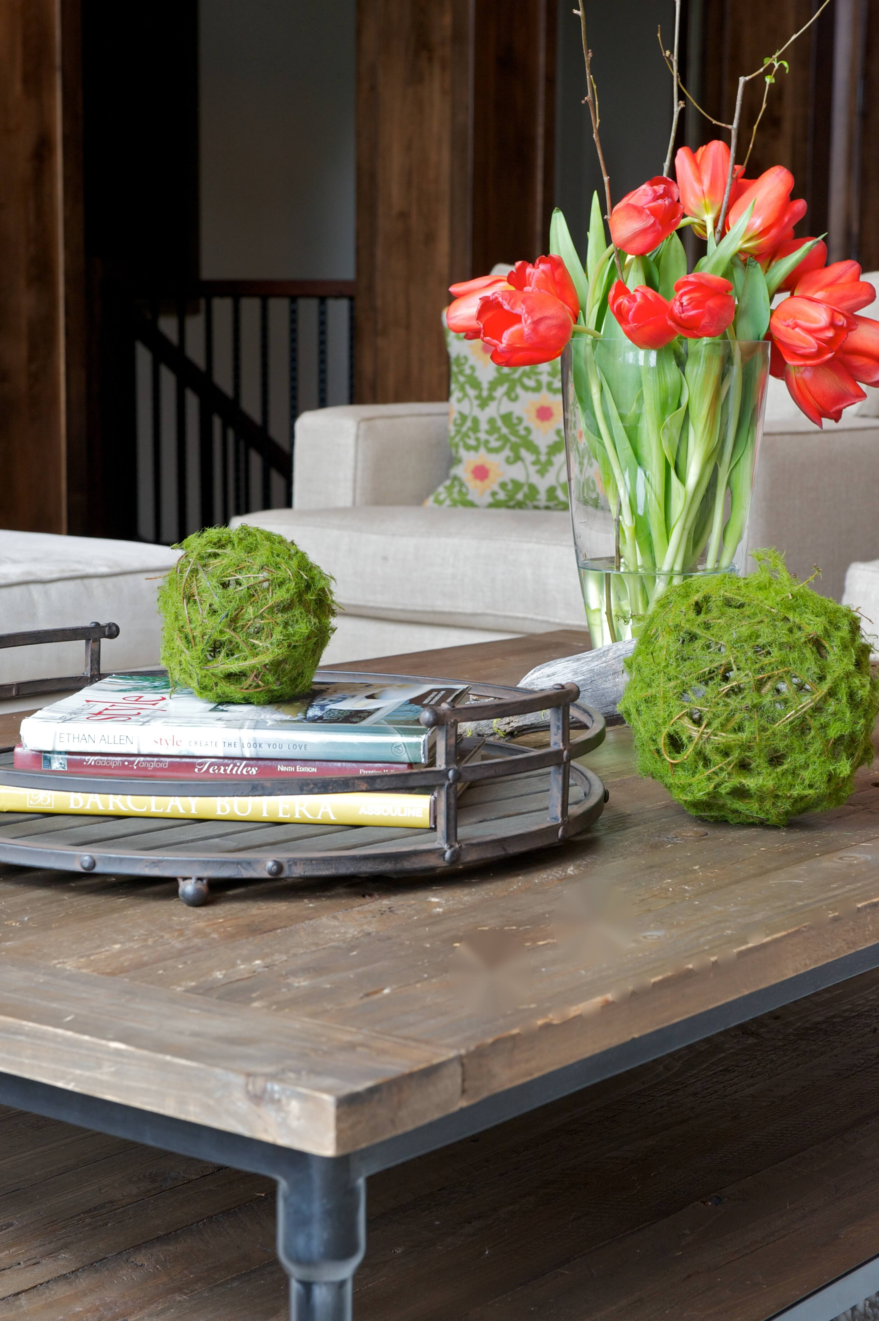 Here we have a close up shot of the coffee table, dark natural wood over black metal frame, with round book holder and green decorative elements. White furniture in background.