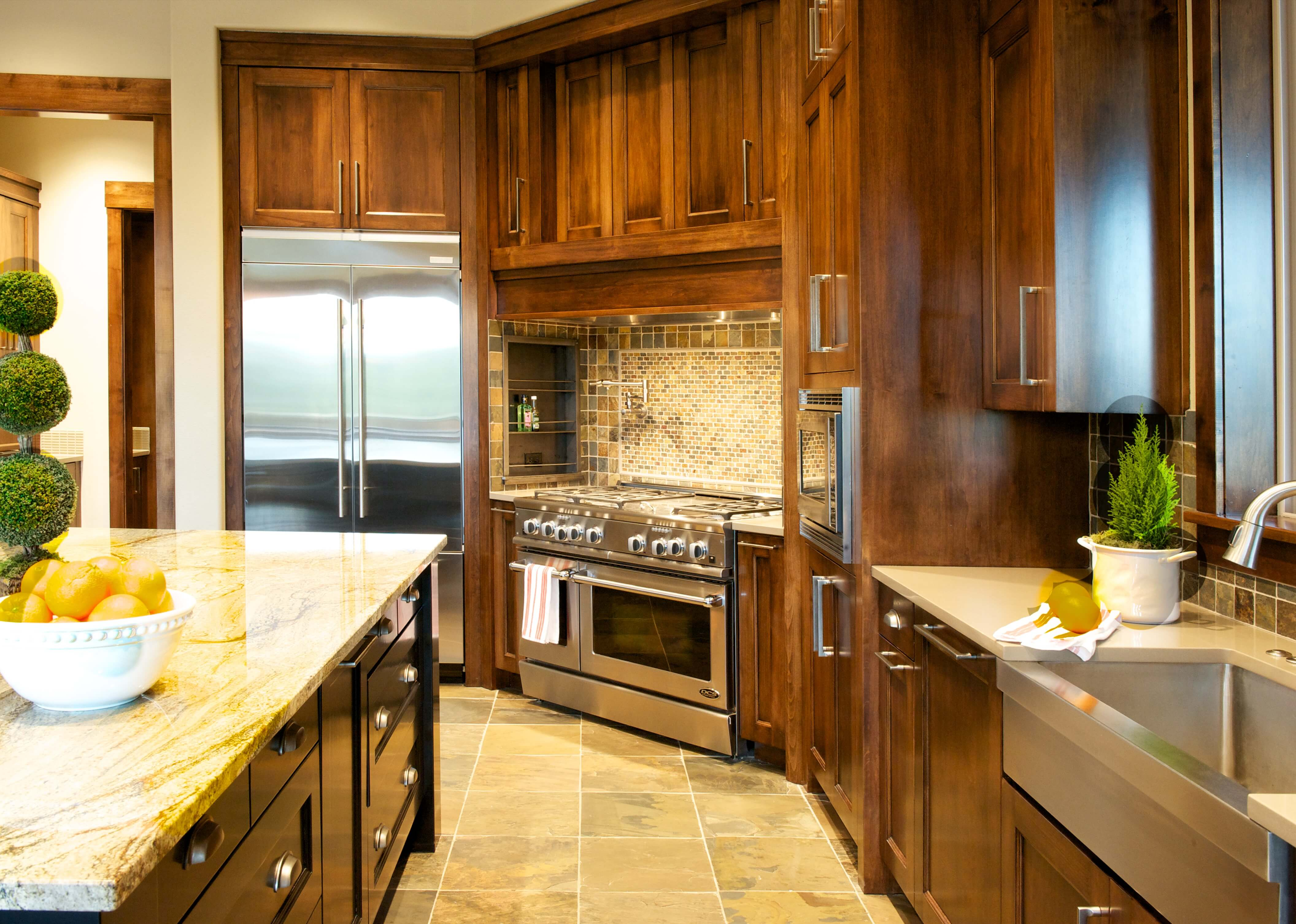 Straight on angle of the kitchen, with detailed view of metal basin sink and matching appliances, with full tile backsplash over range featuring shelving on the side.