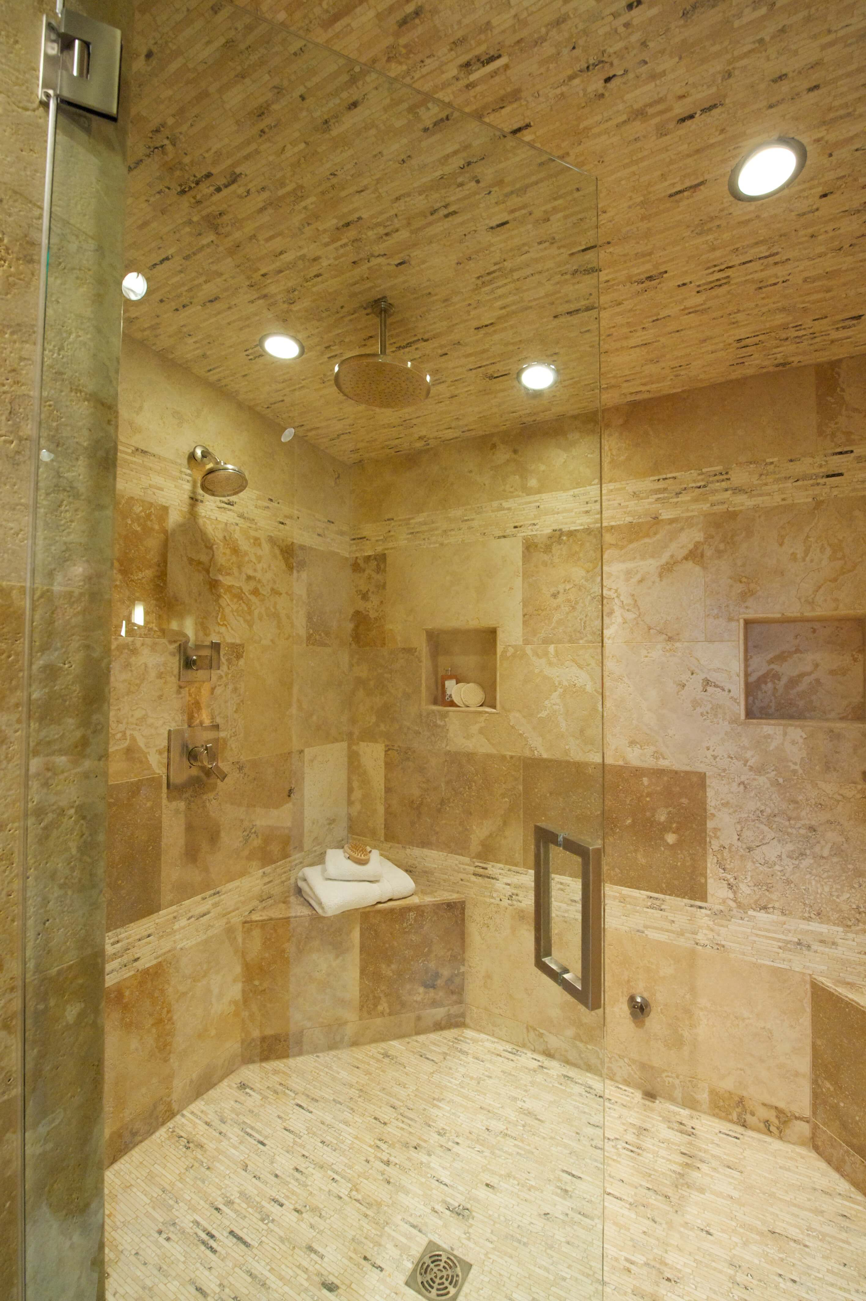 View of the large glass-door shower enclosure done entirely in earth-tone tile as the rest of the bathroom. Recessed lighting and useful shelving built in.