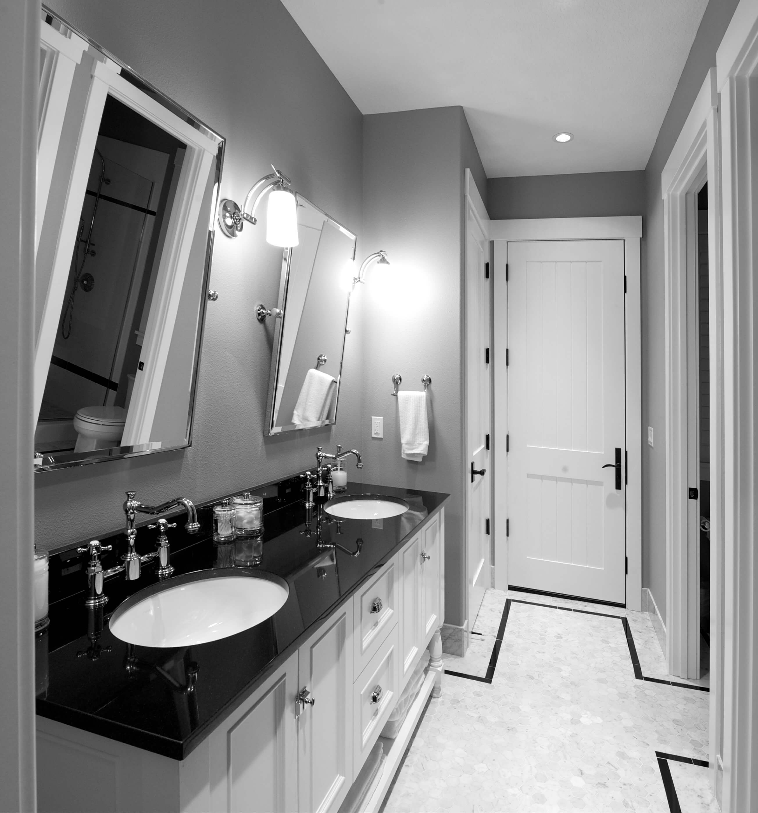 Here's a wide angle of another bathroom in black and white. Chromed tilt-angle mirrors hang over black countertops with traditional basin sinks; patterned tile flooring mirrors the color scheme.