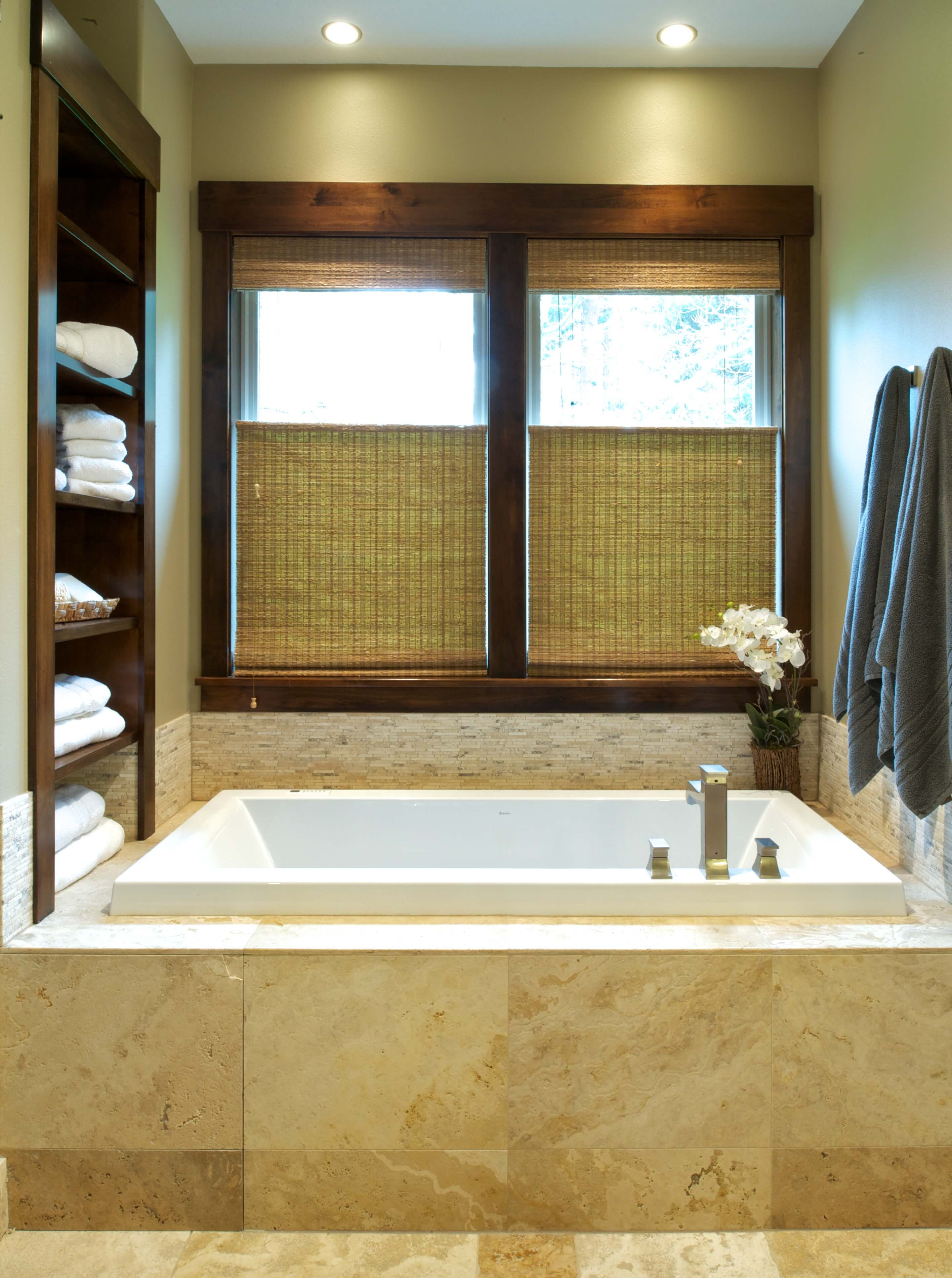 This close up view of the bathtub highlights the unique angular faucet design and mini-tile backsplash beneath large windows with rich wood molding.