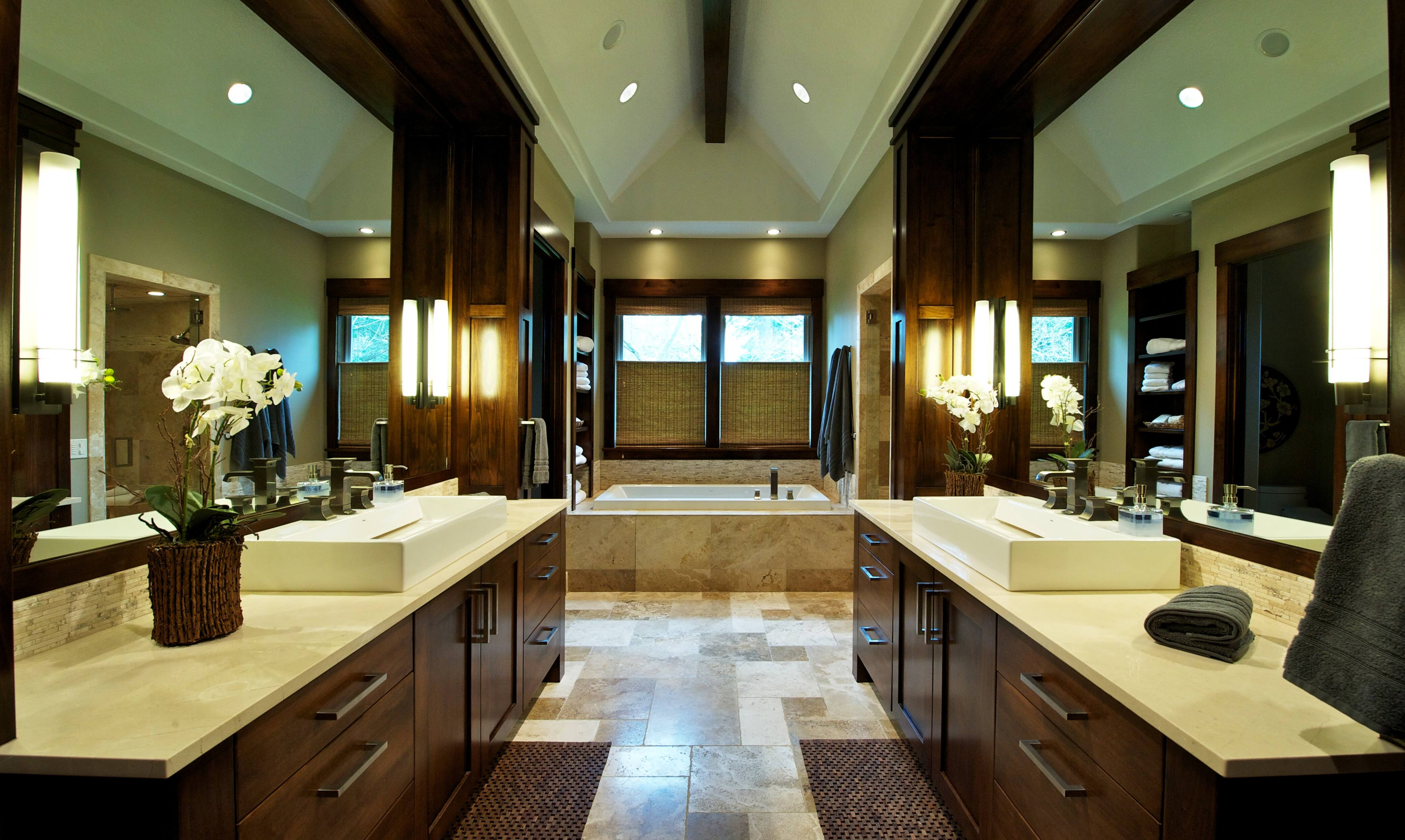 The primary bath is replete with twin rich, dark wood cabinetry and mirror surrounds over earth tone tile flooring with large bath in background. Single exposed beam runs down length of vaulted ceiling.