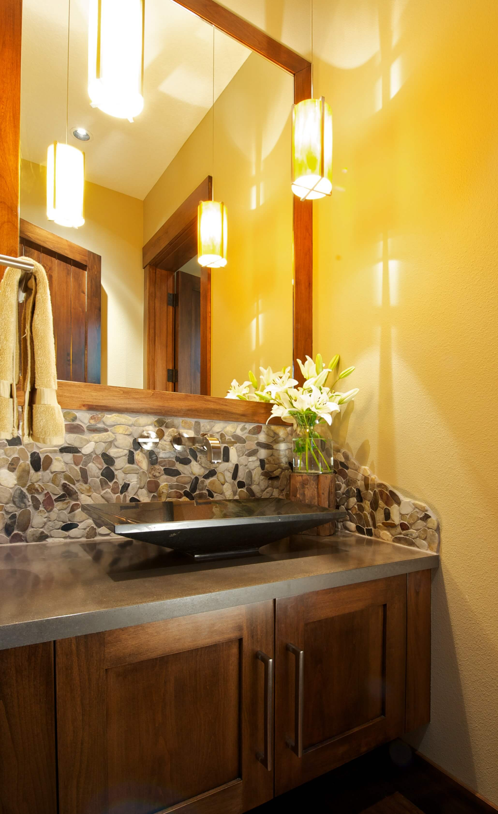 Guest bathroom vessel sink over slate grey countertop with wood cabinetry features stone pattern backsplash beneath mirror.