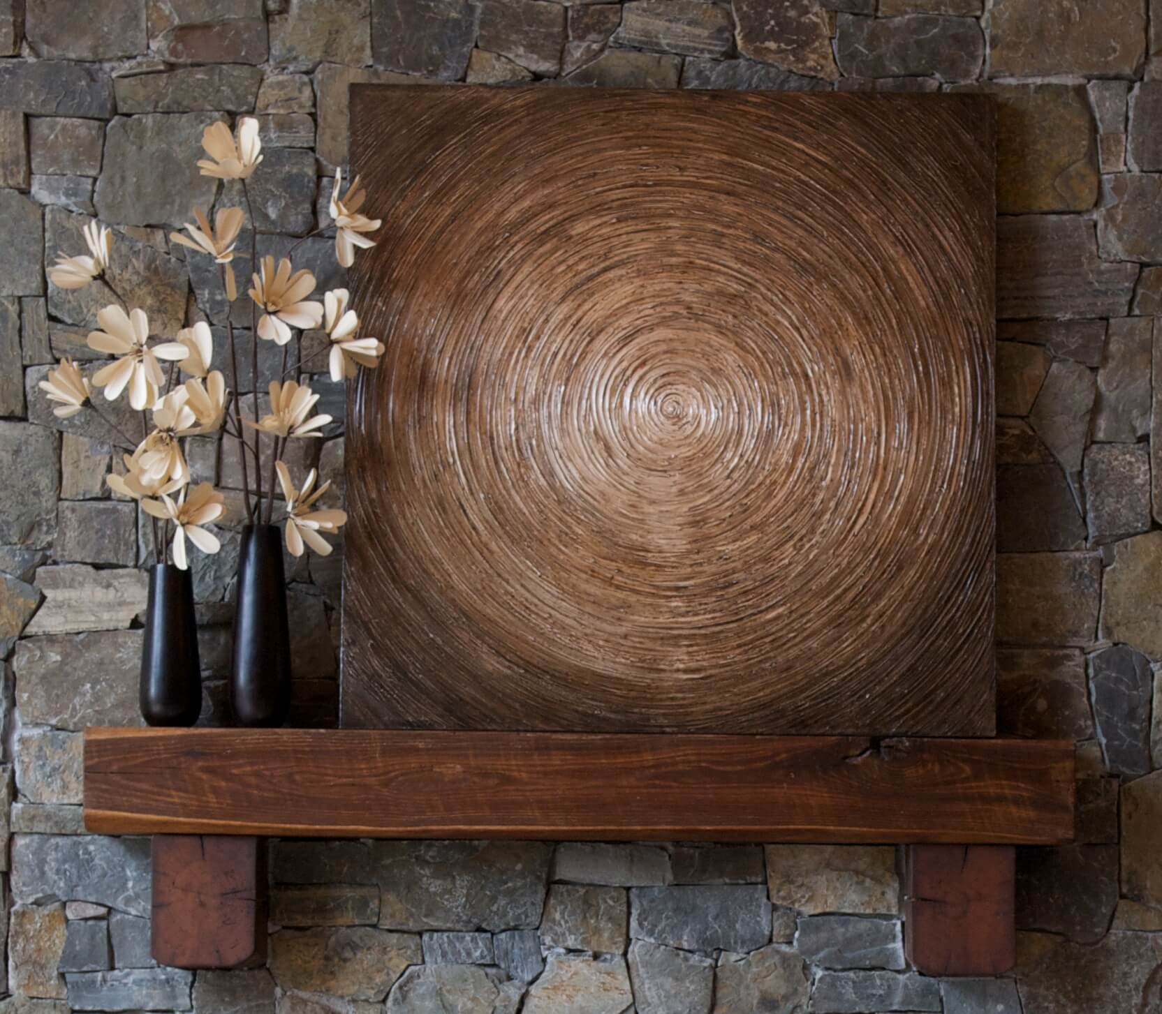 Wood mantle piece holds this unique swirled art piece over ceiling height stone fireplace surround.