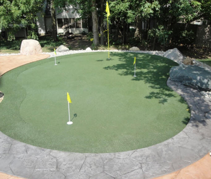 This kidney shaped custom green stands apart from forested space with large stone tile border in grey and sand colors.