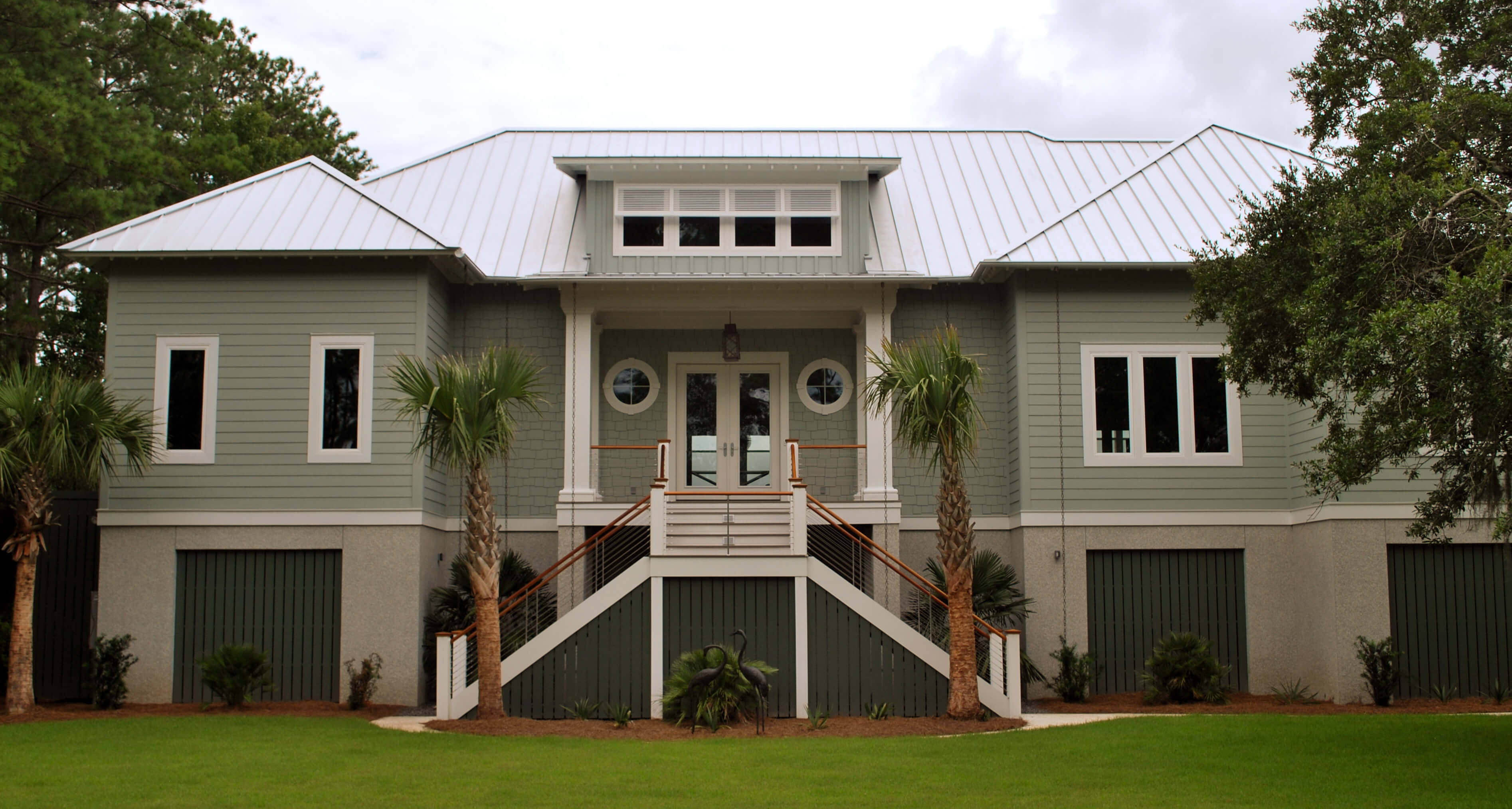 Front view of house with upper level split-stair entrance way and twin port windows.