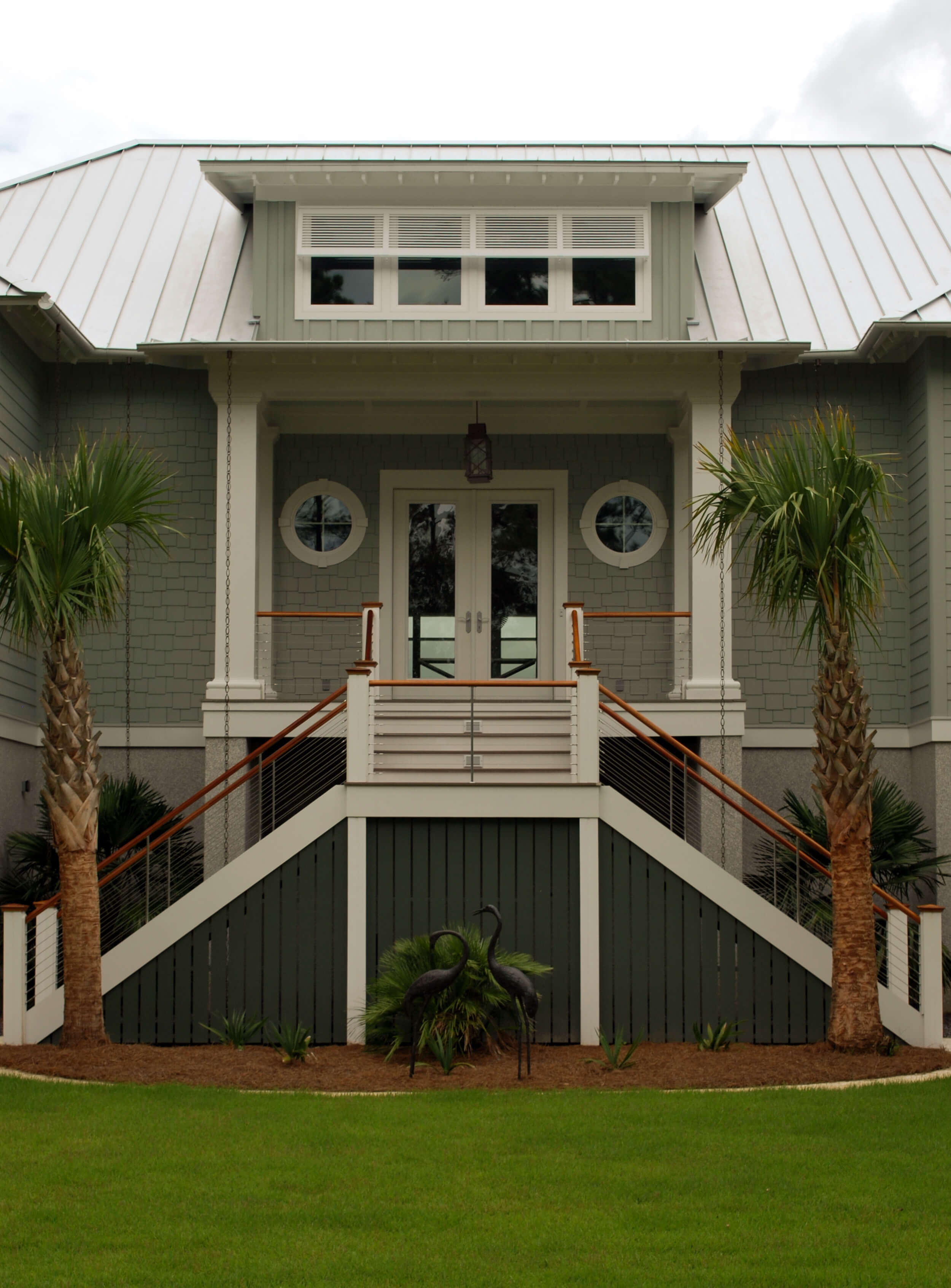 Head-on view of front staircase. Port windows and palm trees accentuate nautical theme.