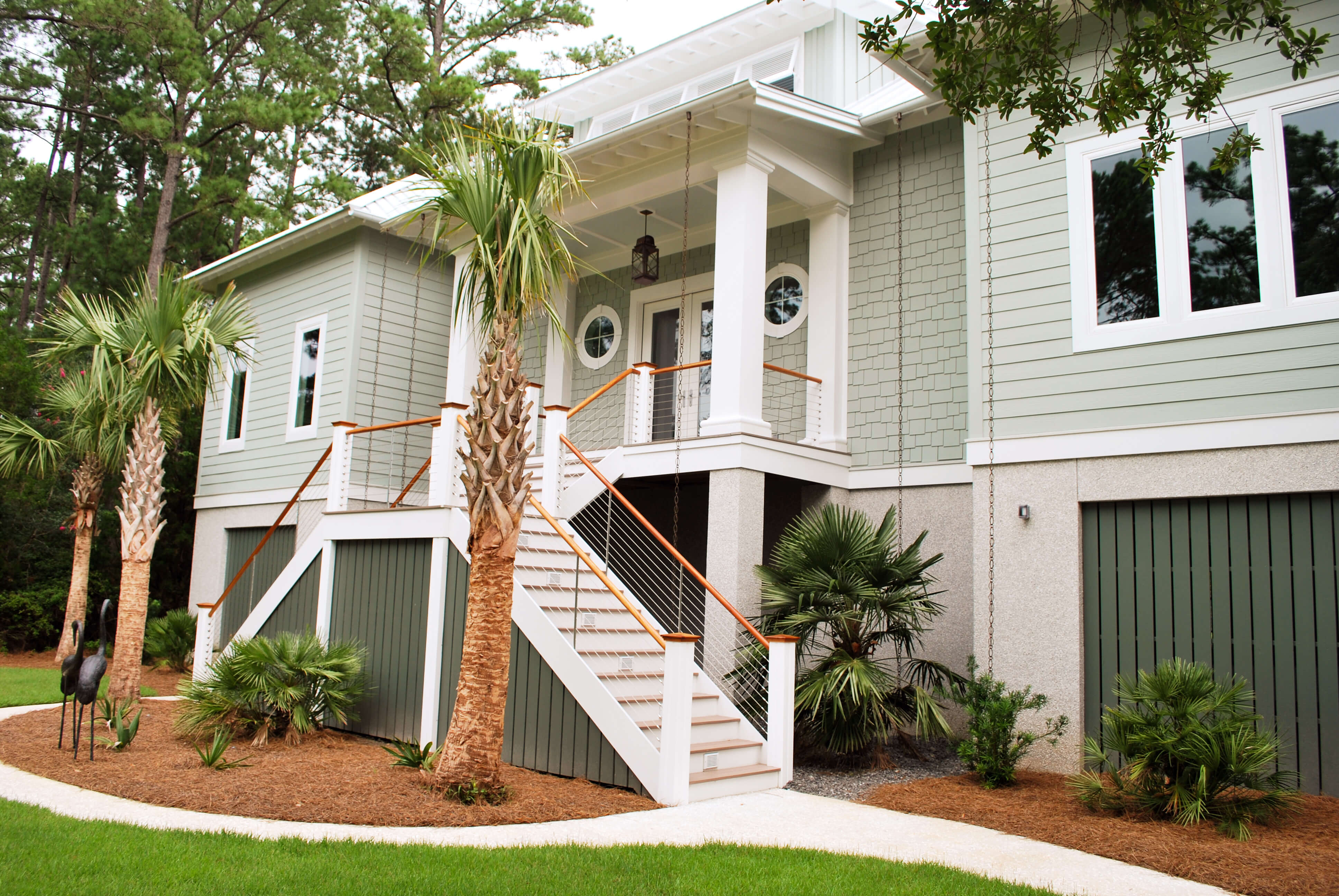 Angled look at front entrance with elaborate, split direction staircase featuring natural wood rails.