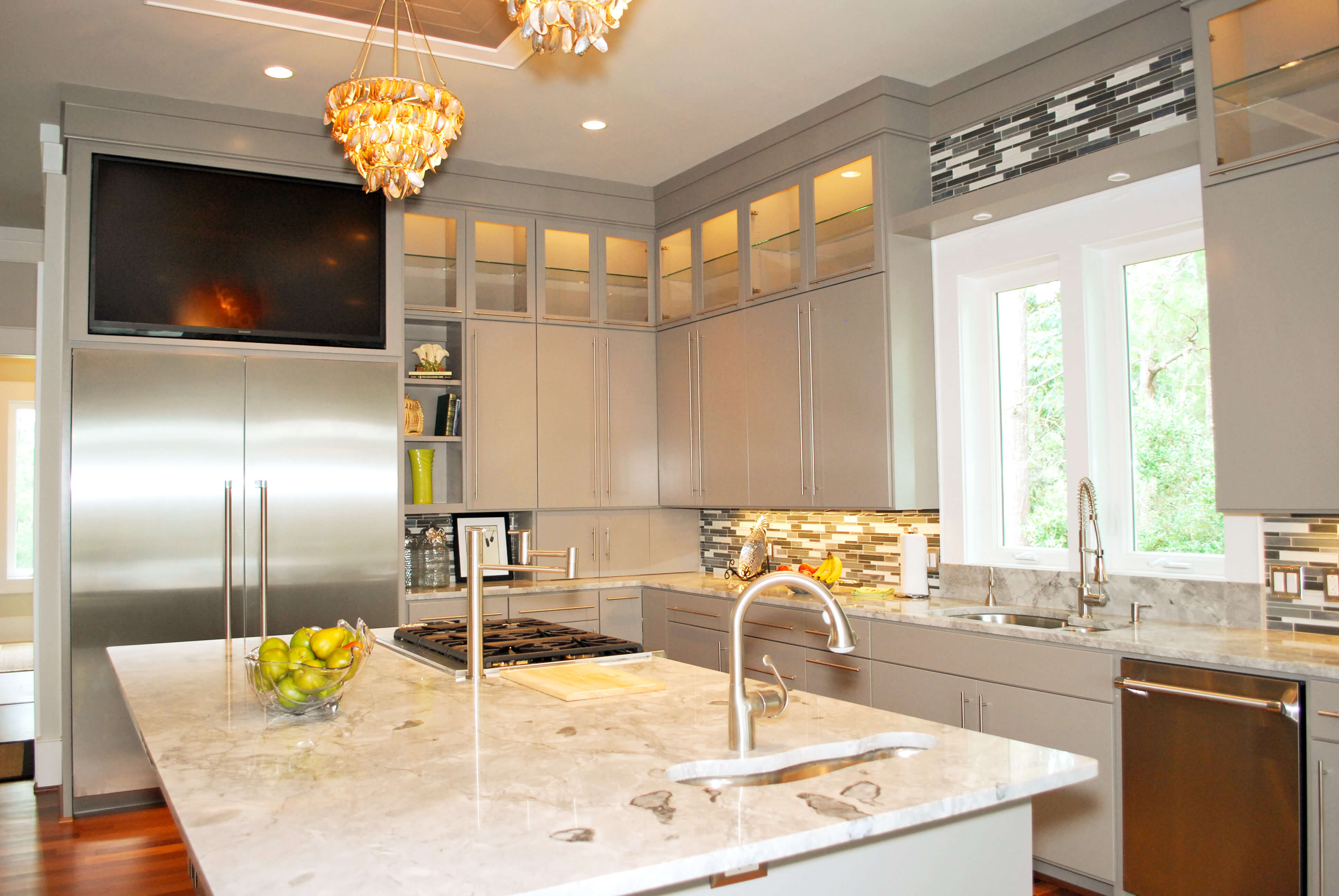Kitchen features minimalist cabinetry with metal handles, marble top counters, tile backsplash and interior lit upper glass cabinets.