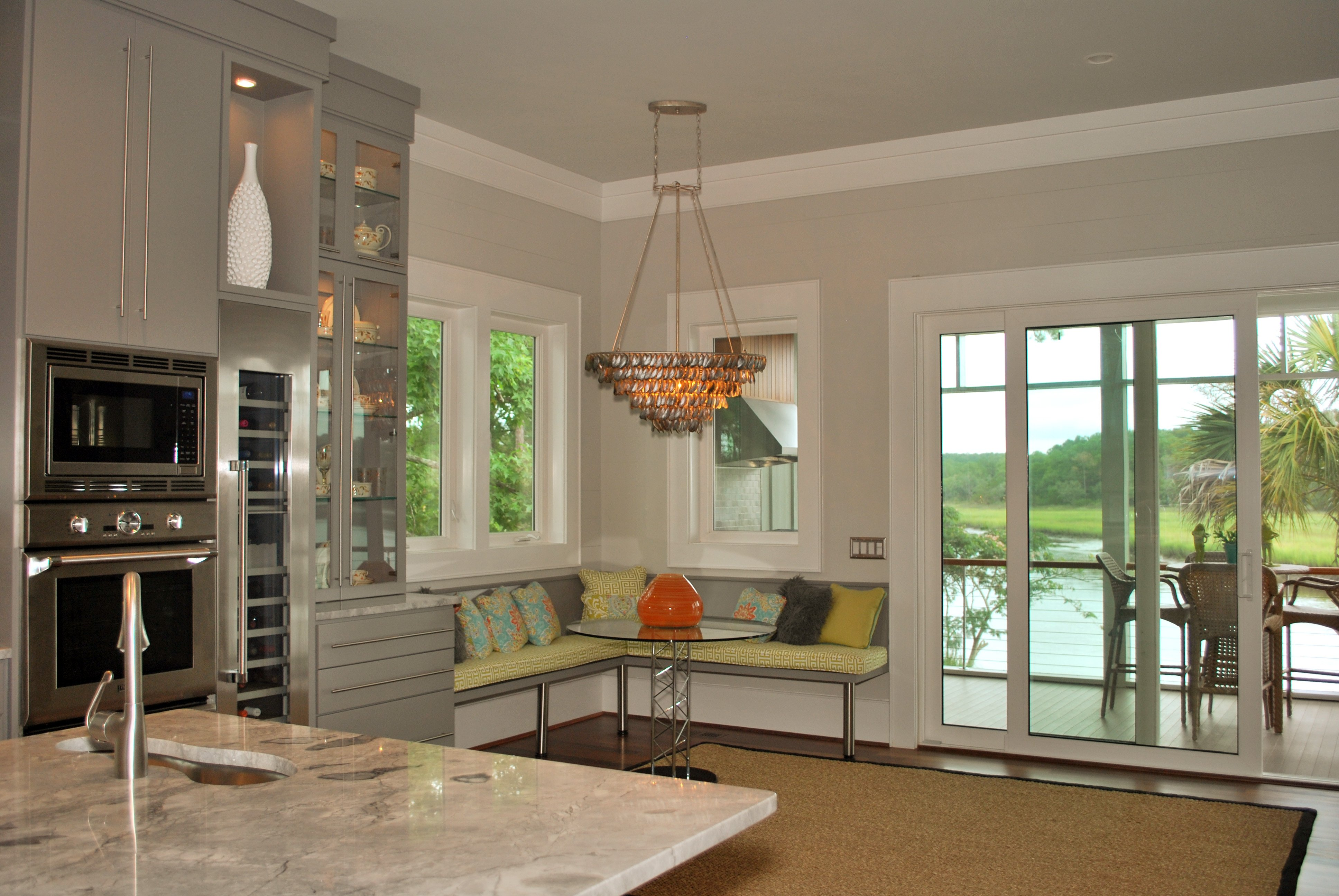 Corner built-in breakfast nook with green cushions and glass table with modern chandelier overhead, sliding glass door to patio on right.