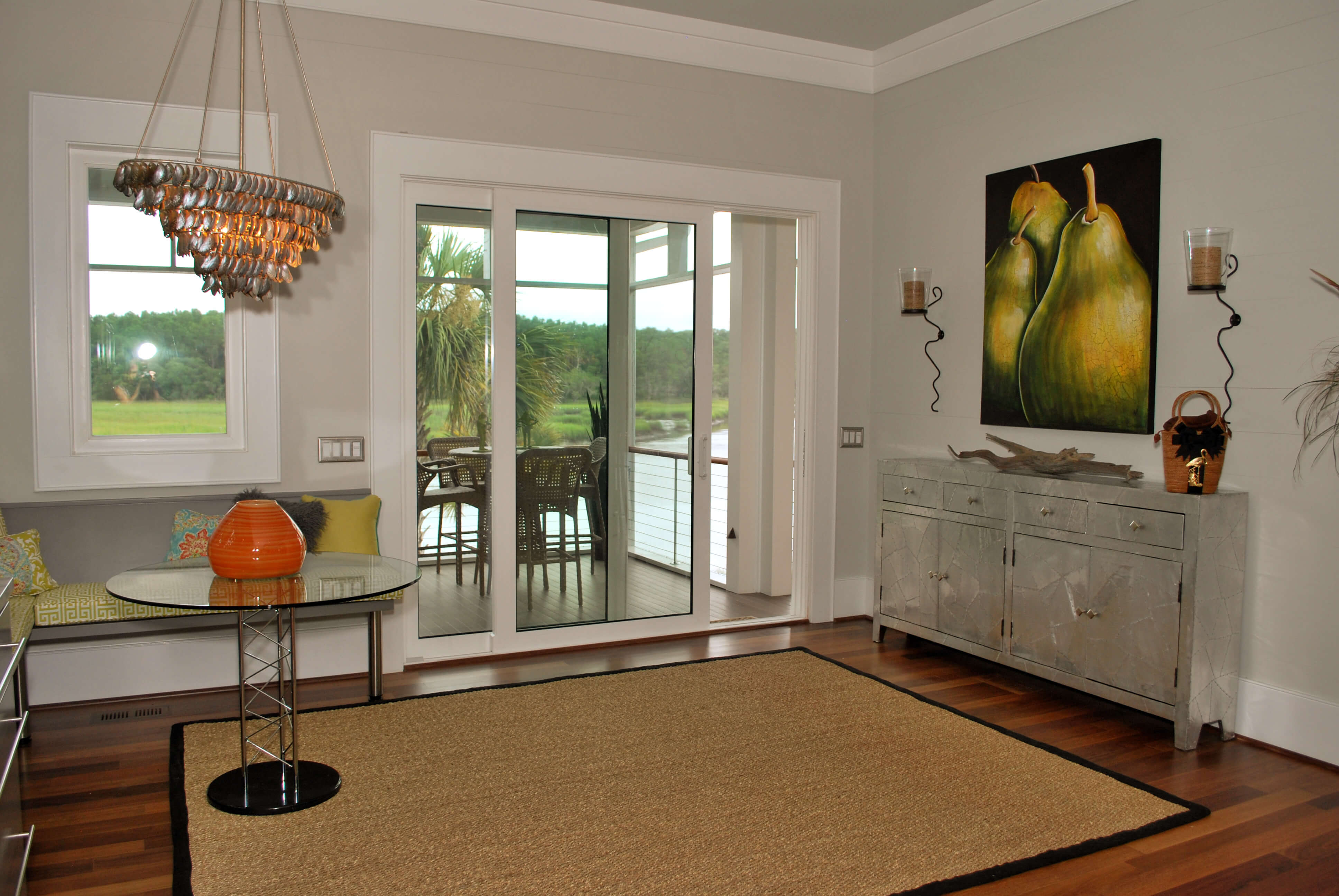 Wider view of nook area off kitchen, with art pieces and grey cabinet, sliding door to second dining area on deck.