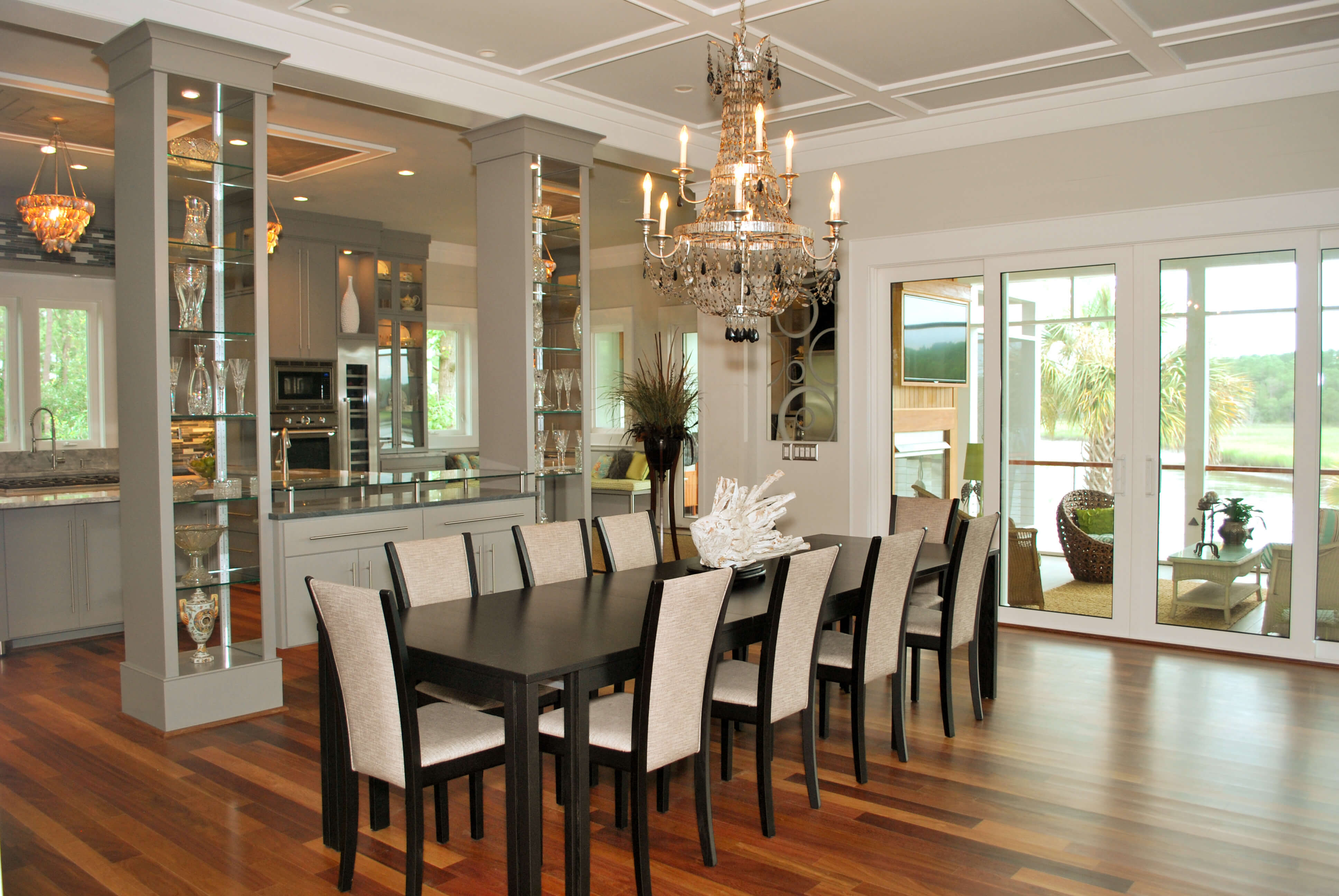 Extra long dining room table in black with black and white chairs, elaborate chandelier overhead, and twin glass-shelved pillars dividing kitchen space.