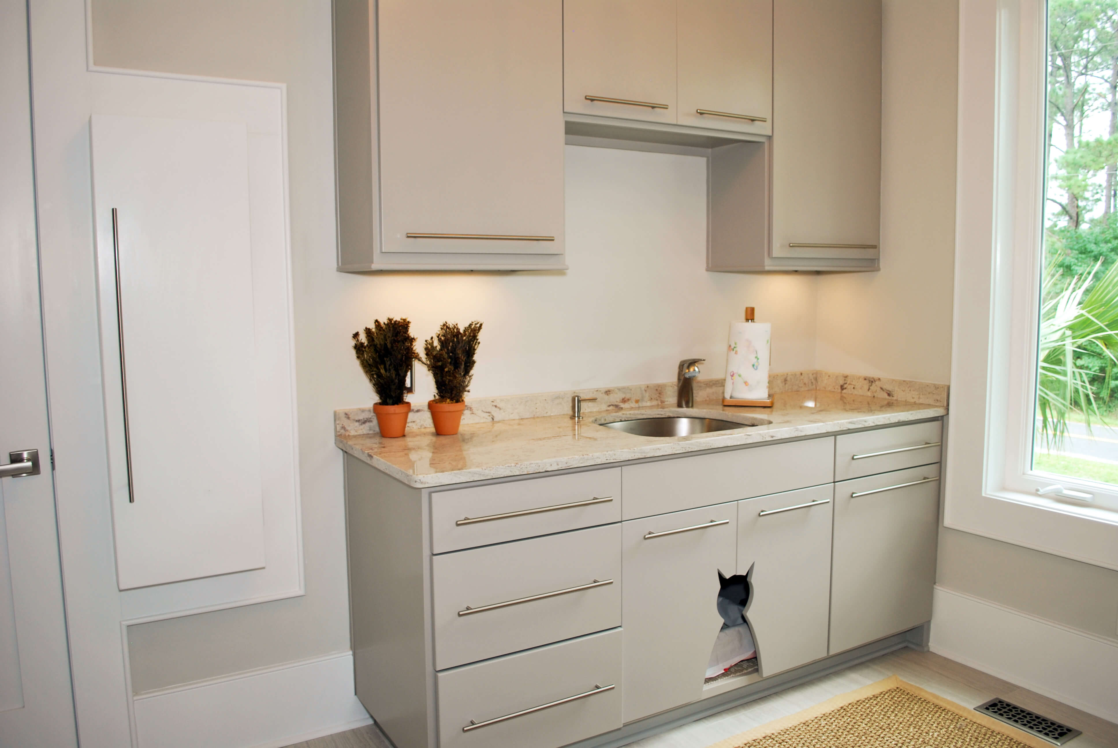 Laundry room features similar cabinetry as the kitchen, with its own marble countertops and sink, with in-cabinet litter box with cat shaped entryway.