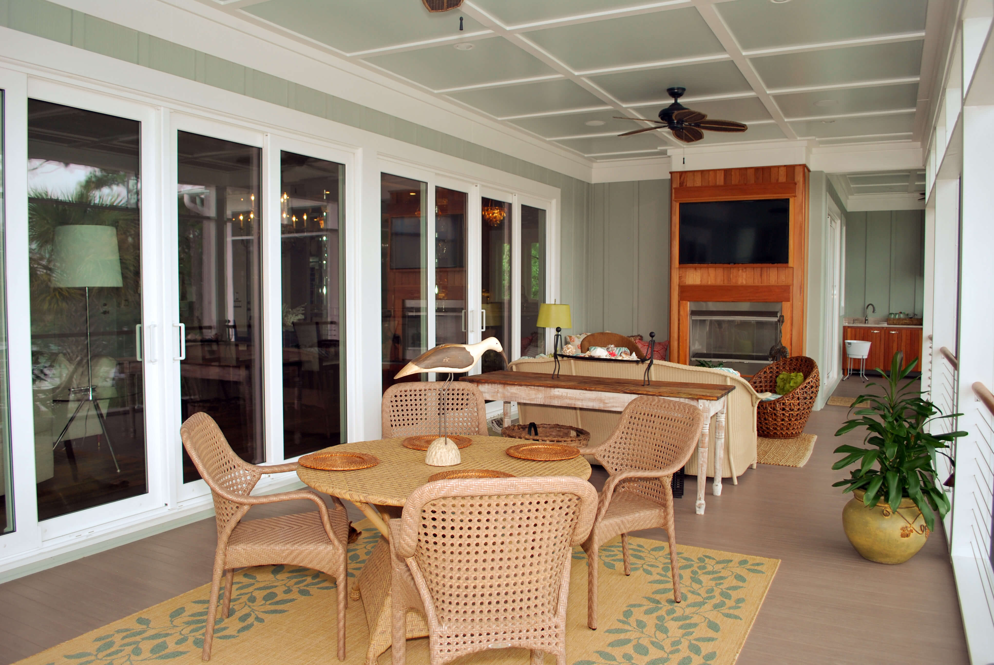 Screened in upper deck with dining area and built-in grill. Sliding glass doors across entire wall.