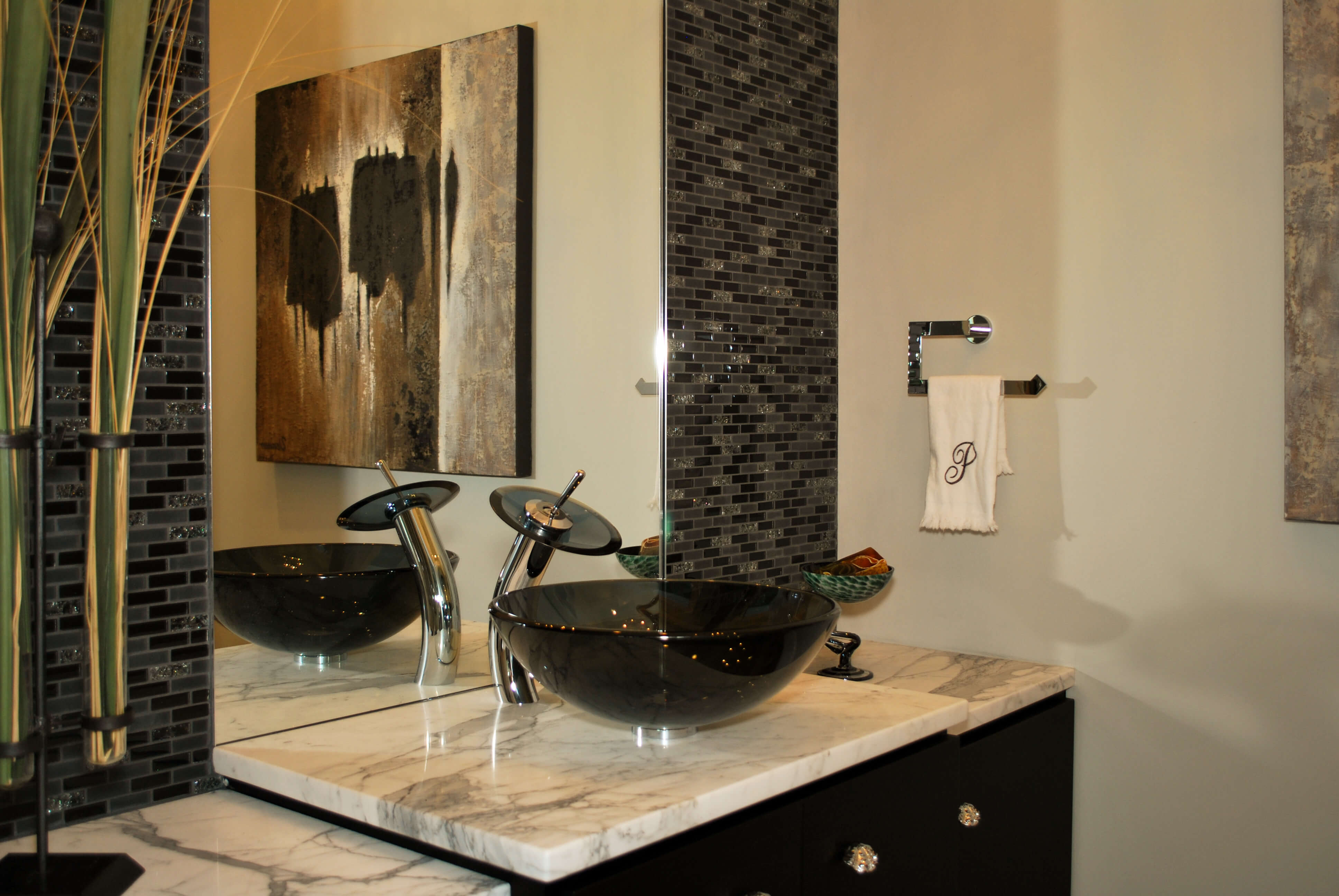 Bathroom features vessel sink over light marble countertop with black cabinetry. Tile backsplash surrounds mirror.