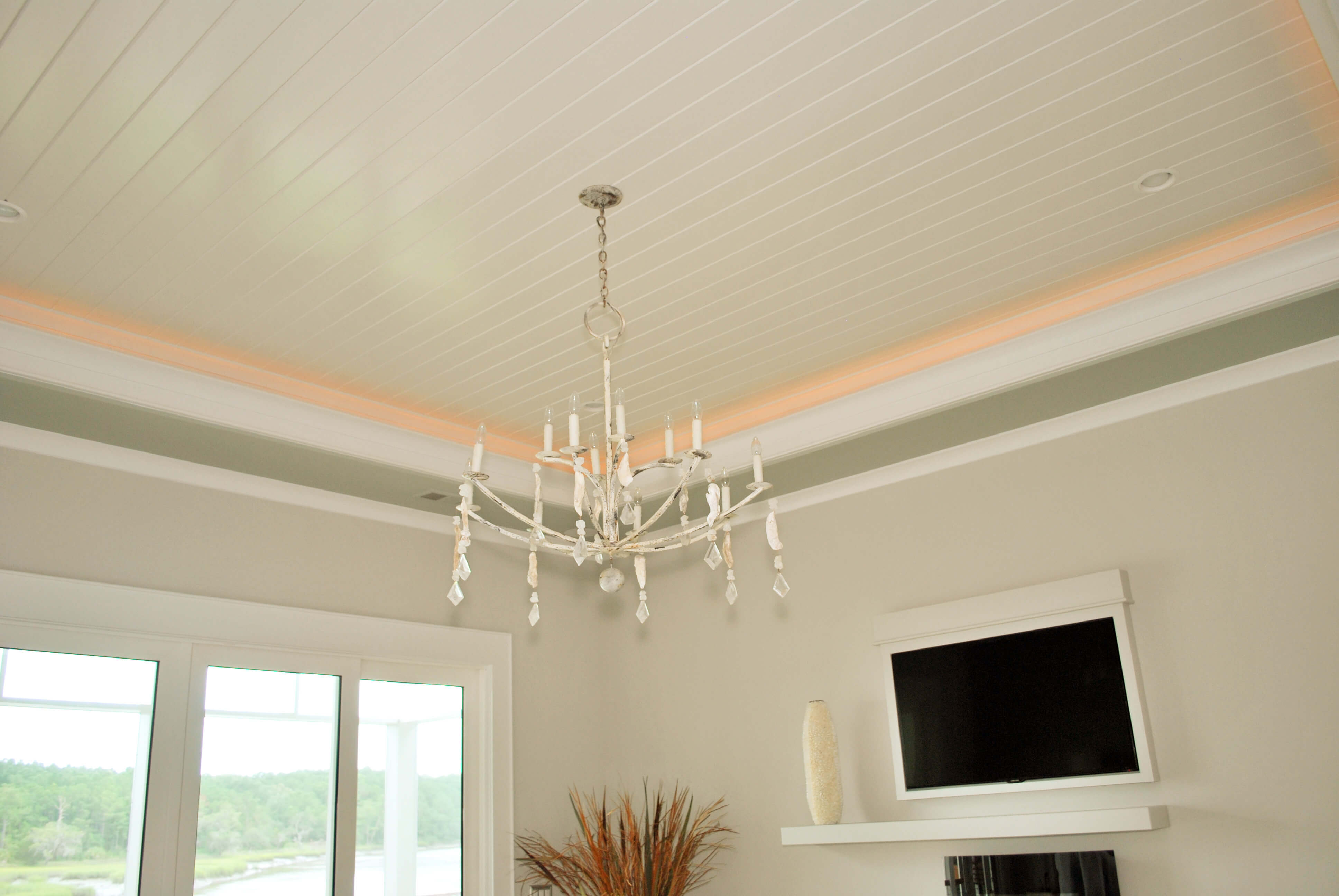 Ceiling in bedroom features wraparound embedded lighting, while wall-mounted TV can be seen beyond minimalist chandelier.