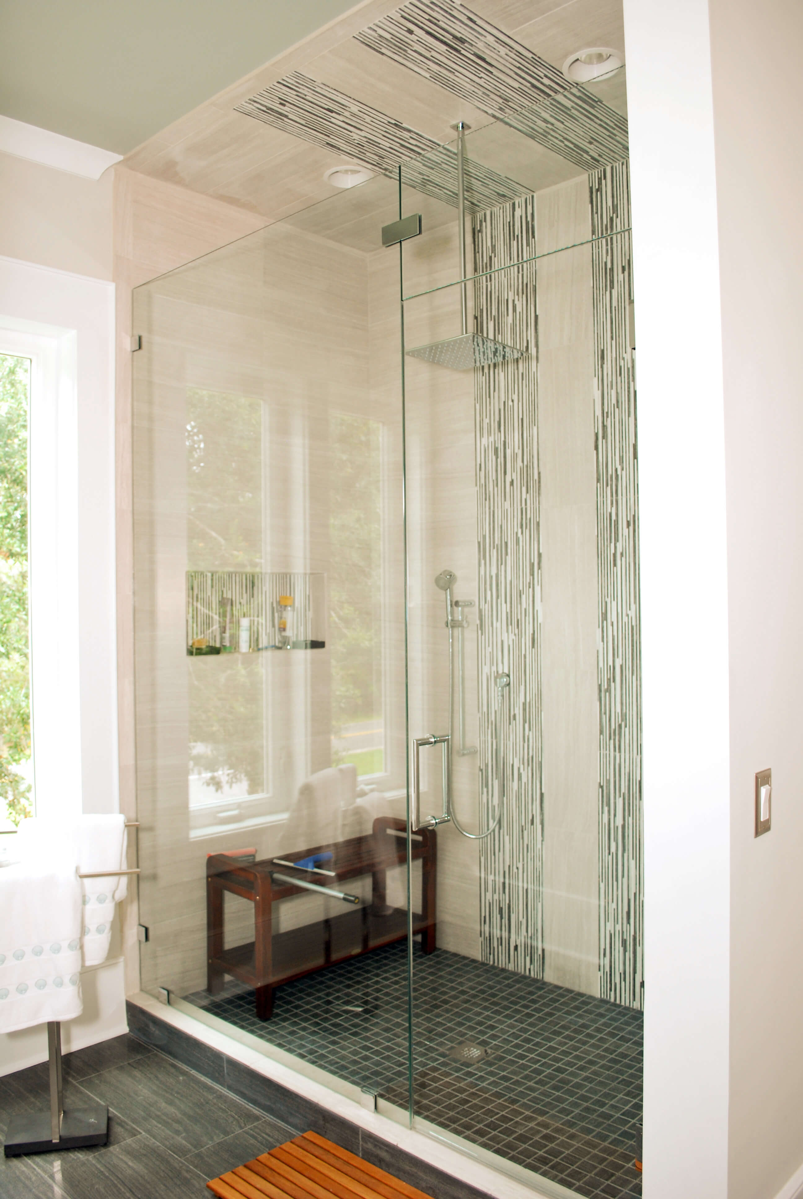 Primary bath features glass door shower with patterned tile accents and wood seating.