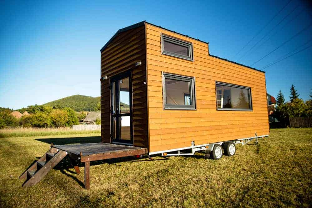 Tiny house with elevated loft area and wood exterior on wheels