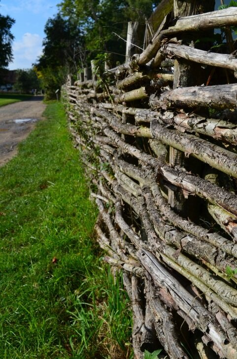 Natural branch fence features entirely untreated wood, with bark remaining, for thick look with minimal gap.