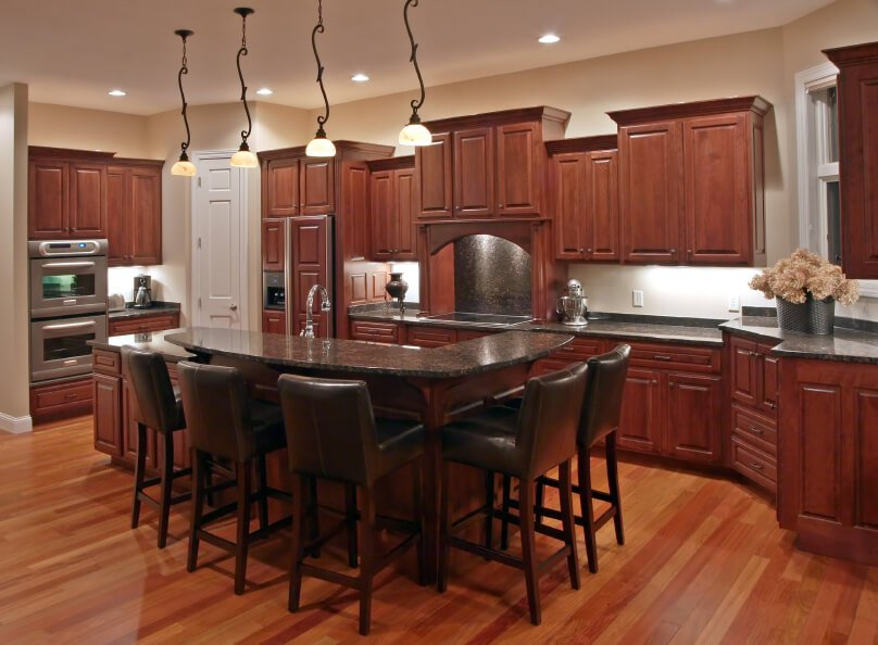 Open design kitchen flush with natural wood: lighter shade hardwood flooring pairs with darker shade cabinetry, punctuated by black marble countertops and backsplash.