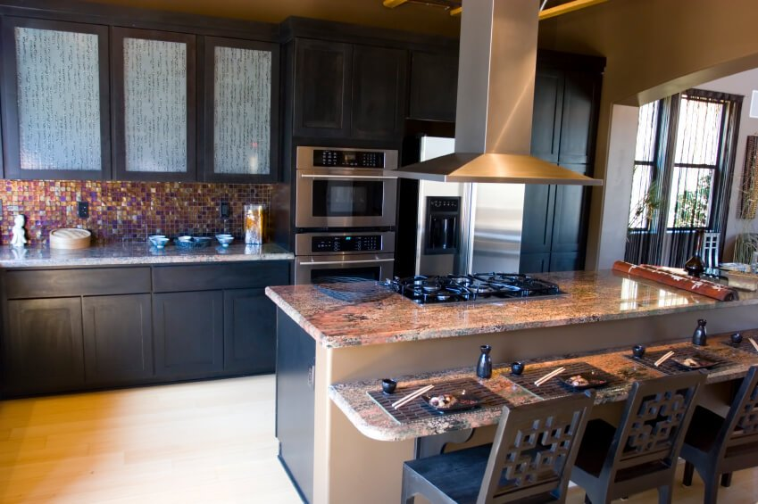 Black painted wood cupboards surround multi-colored mosaic tile backsplash and salmon toned marble countertops in this kitchen with light hardwood flooring.