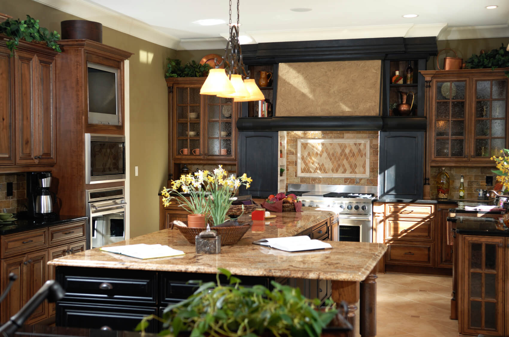 Black wood cabinetry surrounds range with beige tile backsplash in this detailed kitchen. L-shaped island features more black paneling, while rest of kitchen is flush with dark natural wood tones.