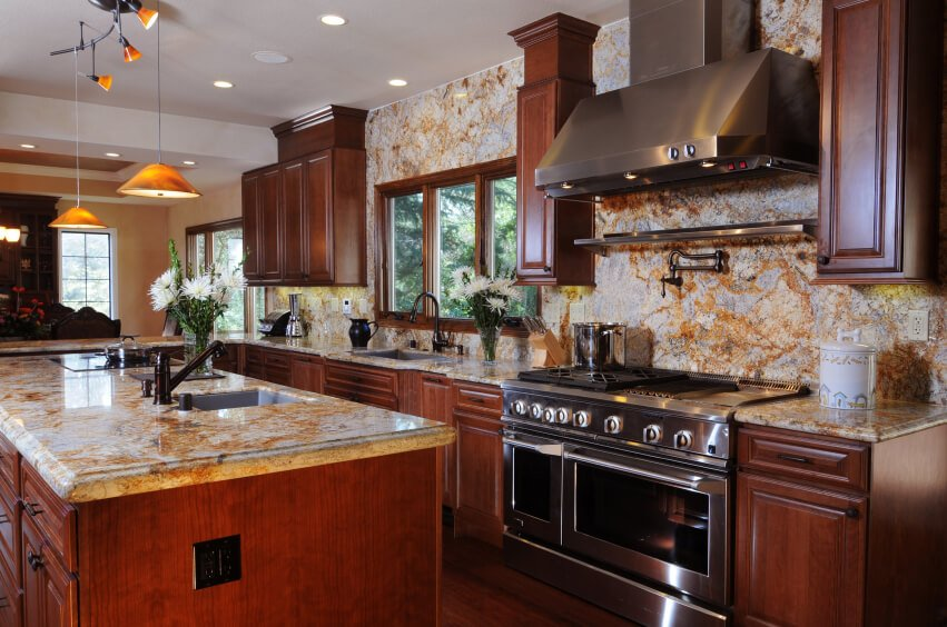 Bold use of light marble on countertops and entire wall extending from backsplash space stands in contrast with cherry wood cabinetry and hardwood flooring through this open plan kitchen.