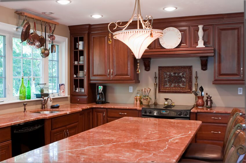 Warm pink marble countertops in this kitchen pair with stained wood cabinetry in this cozy kitchen under ornate chandelier.