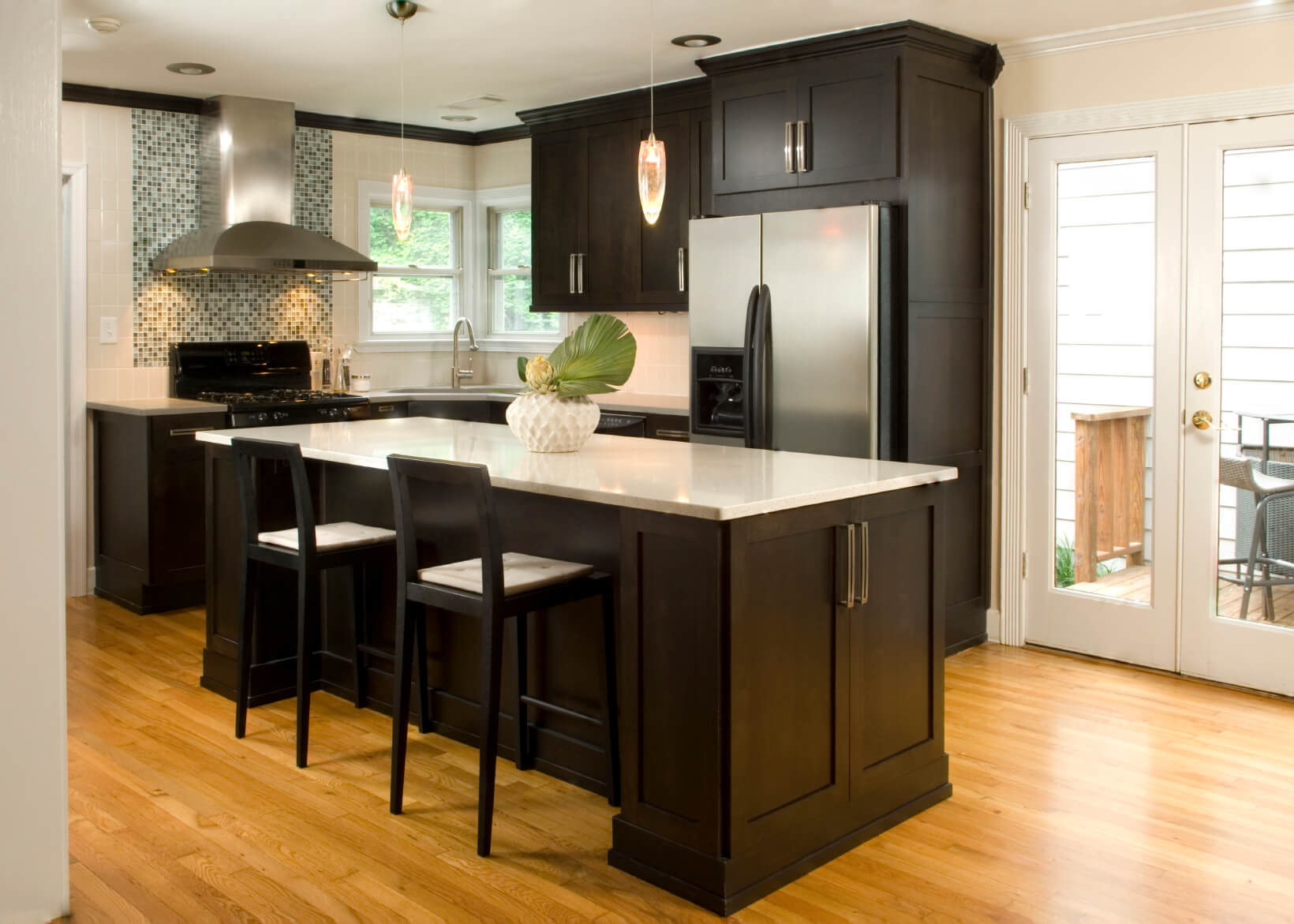High contrast white wall kitchen with dark wood paneling and cupboards, paired with white countertops and light hardwood floor.