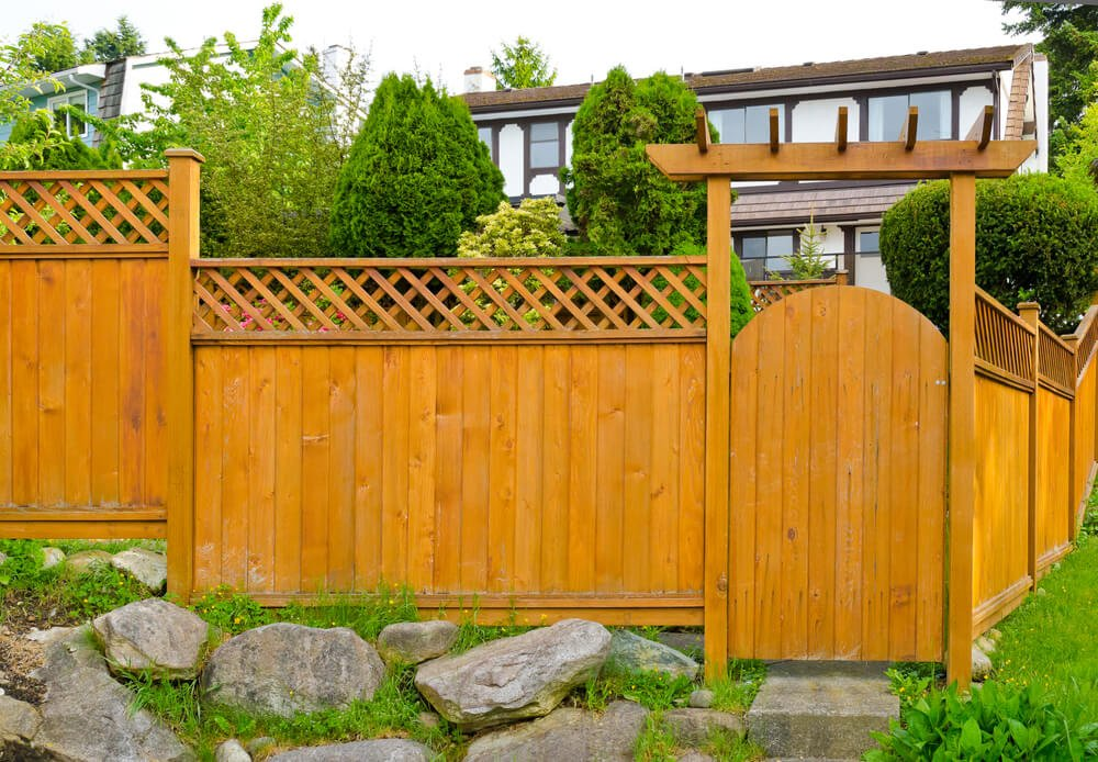 This light natural wood fence features Eastern-style arch over corner gate entry and lattice style upper detail.