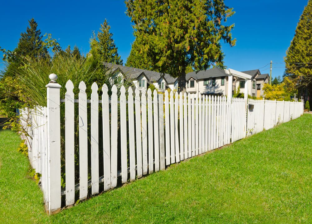 This rounded spike top white fence features large flat arch over gateway.