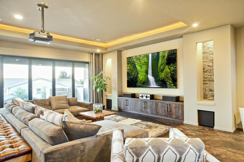 Earth tones throughout this living room, featuring grey L-shaped sectional on brown marble flooring, centered around natural wood coffee table. Natural wood media center beneath large projection screen sits across from furniture over shag area rug.